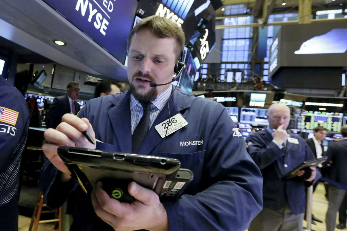 Trader Michael Milano, left, works on the floor of the New York Stock Exchange Friday.