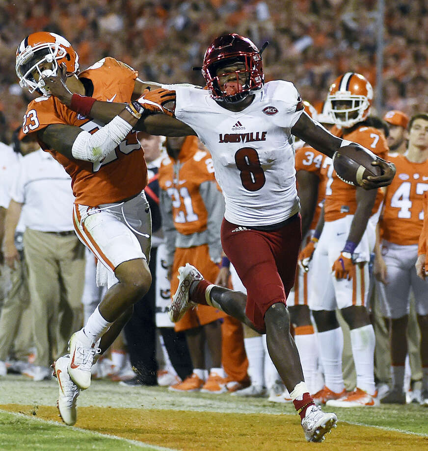 In this Oct. 1, 2016, photo, Louisville quarterback Lamar Jackson (8) stiff-arms Clemson safety Van Smith (23). Jackson was selected the Walter Camp Player of the Year Thursday. Photo: Rainier Ehrhardt -The Associated Press  / FR155191 AP