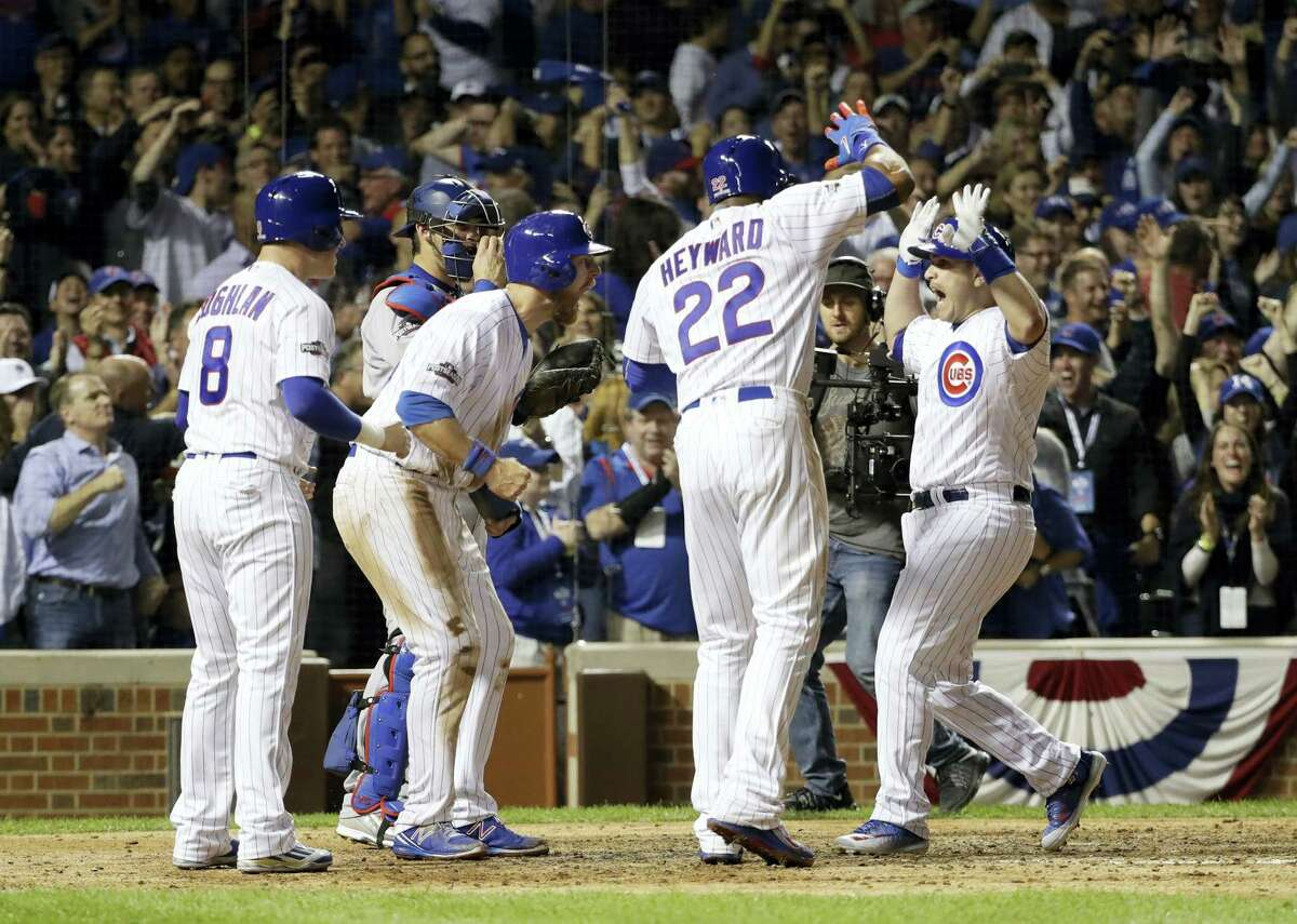 Chicago Cubs catcher Miguel Montero, right, celebrates after hitting a grand slam during the eighth inning of Game 1 of the NLCS on Saturday.