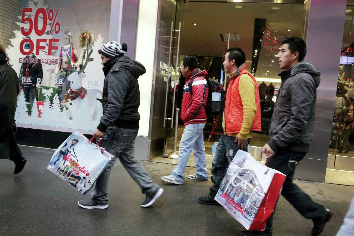 In this Dec. 2, 2015 photo, shoppers carry their shopping bags as they leave the Aeropostale clothing store in New York's Times Square.