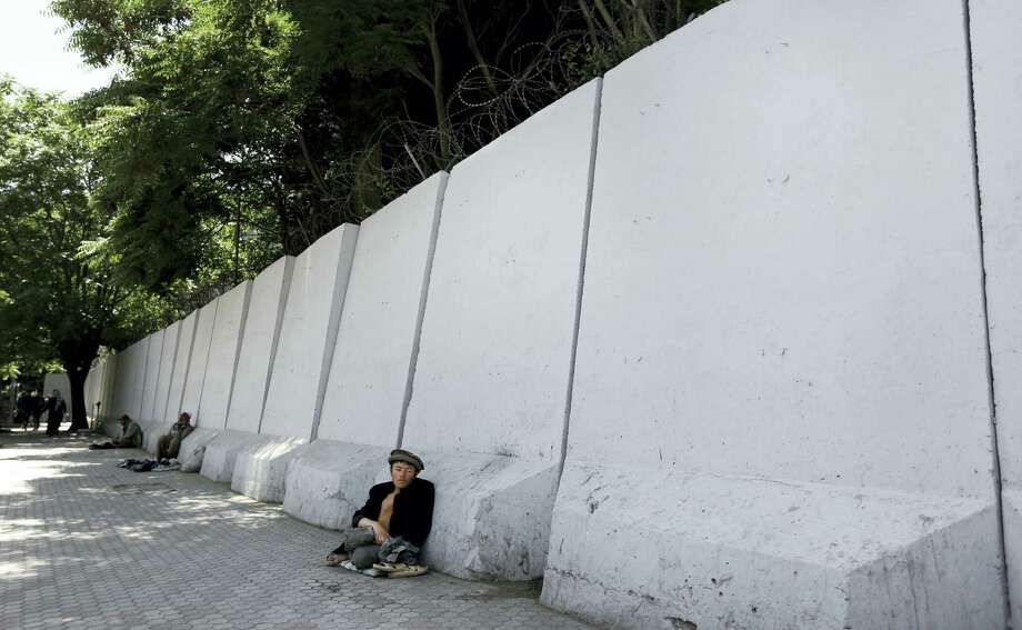 In this Wednesday, May 25, 2016, photo, an Afghan bigger sits in front of blast walls installed to cordon off the Ministry of Communications in Kabul, Afghanistan. With every terrorist attack in Kabul, a little more of what made Afghanistan's capital a garden city of the 1960s disappears behind massive concrete walls designed to thwart suicide bombers and keep the people and buildings behind them safe. Photo: AP Photo/Rahmat Gul   / Copyright 2016 The Associated Press. All rights reserved. This material may not be published, broadcast, rewritten or redistribu