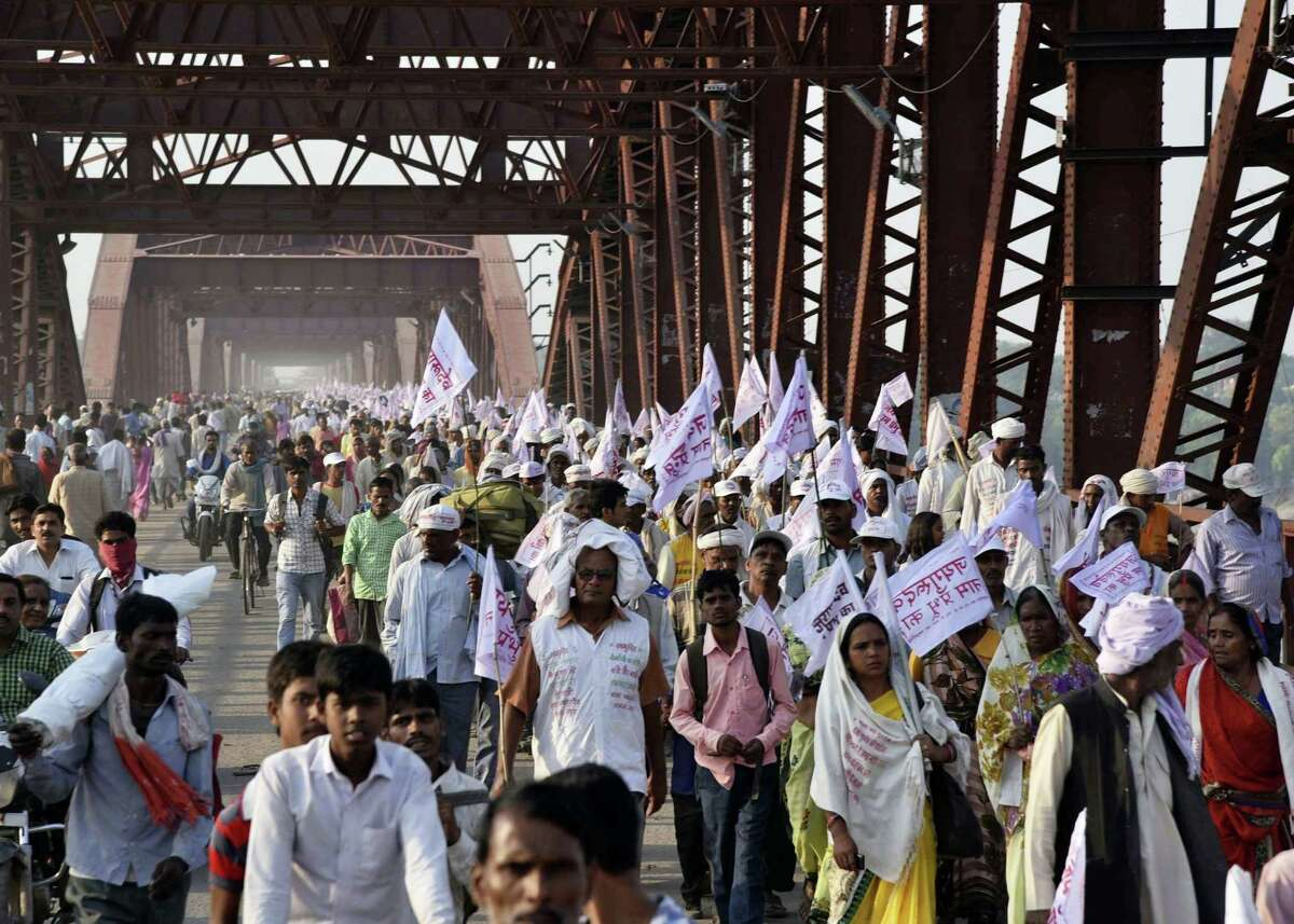 Hindu pilgrims hold religious flags and walk on a crowded bridge after a stampede on the same bridge on the outskirts of Varanasi, India, Saturday, Oct. 15, 2016. More than a dozen people were killed and several more injured in a stampede that occurred as they were crossing a crowded bridge Saturday to reach the venue of a Hindu religious ceremony in northern India, police said. Deadly stampedes are fairly common during Indian religious festivals, where large crowds gather in small areas with few safety or crowd control measures.