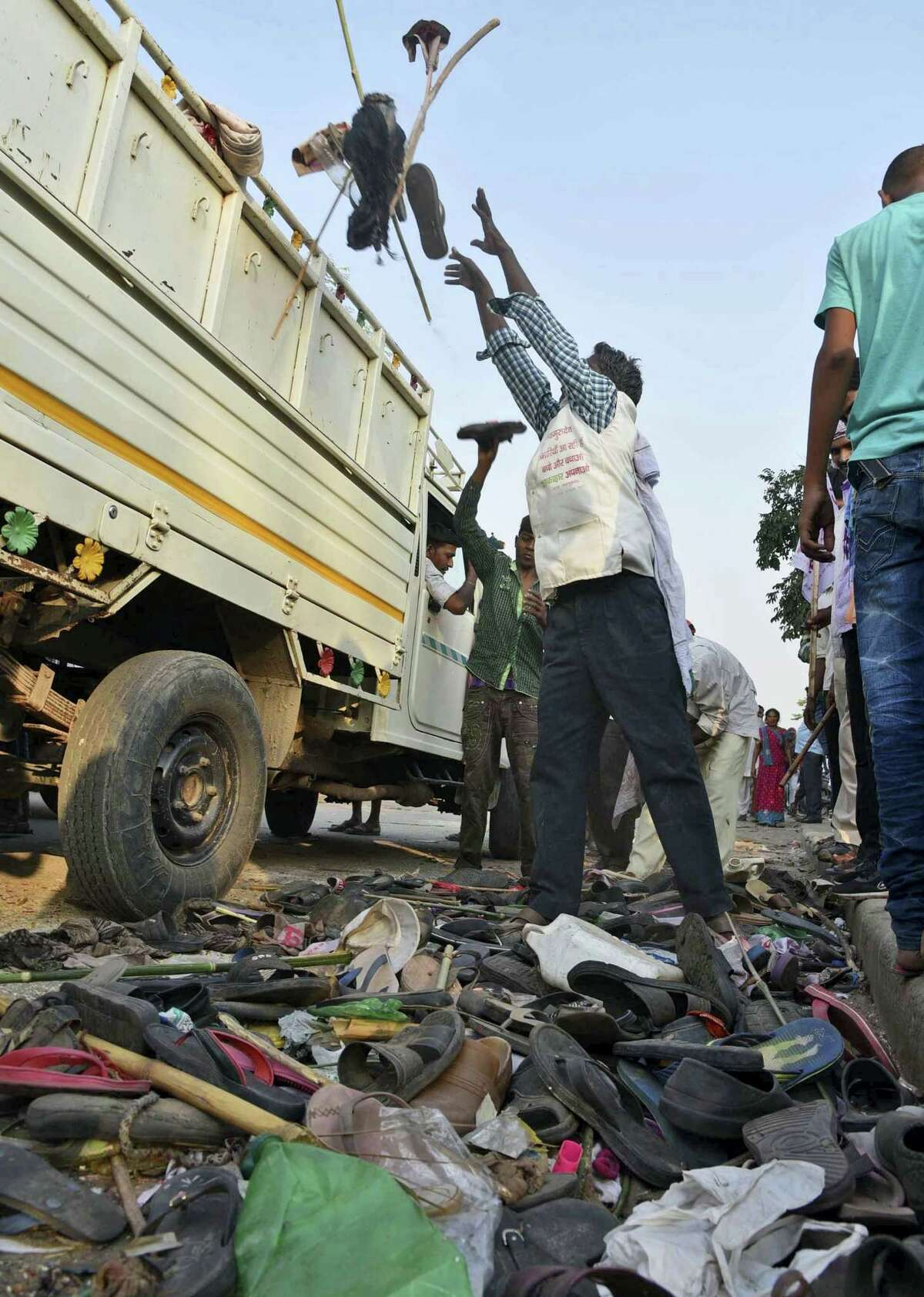 A man loads a truck with footwear of victims of a stampede on a crowded bridge on the outskirts of Varanasi, India, Saturday, Oct. 15, 2016. More than a dozen people were killed and several more injured in a stampede that occurred as they were crossing a crowded bridge Saturday to reach the venue of a Hindu religious ceremony in northern India, police said. Deadly stampedes are fairly common during Indian religious festivals, where large crowds gather in small areas with few safety or crowd control measures.