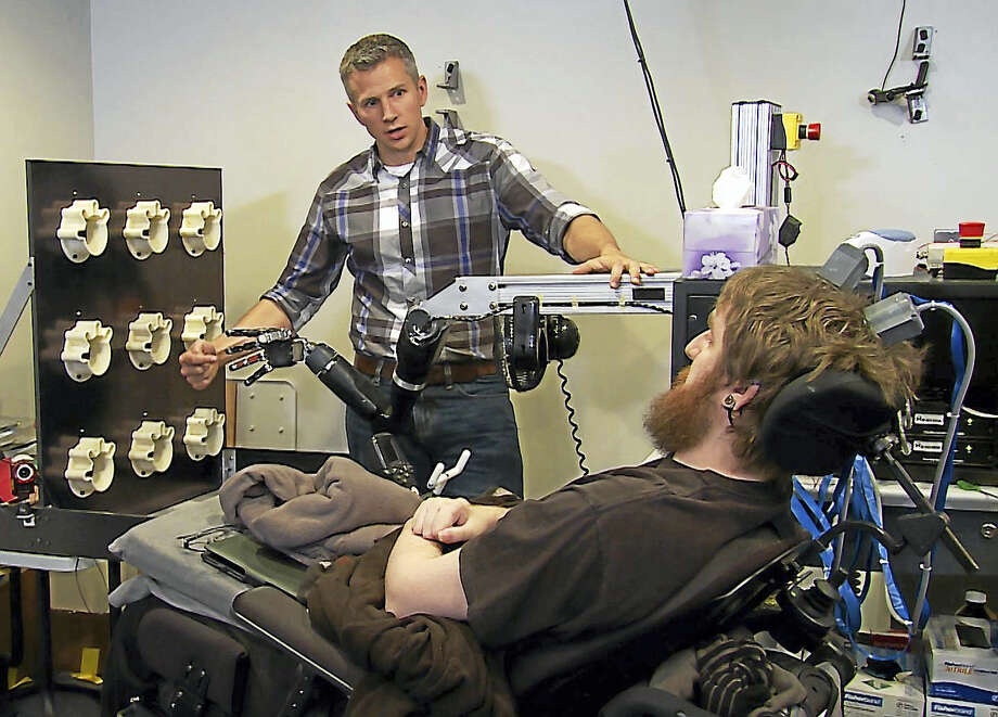 University of Pittsburgh Medical Center researcher Robert Gaunt touches the finger of a robotic arm, causing Nathan Copeland, a quadriplegic, to feel that sensation in his own finger.  UPMC — Pitt Health Sciences. Photo: UPMC - Pitt Health Sciences / The Washington Post
