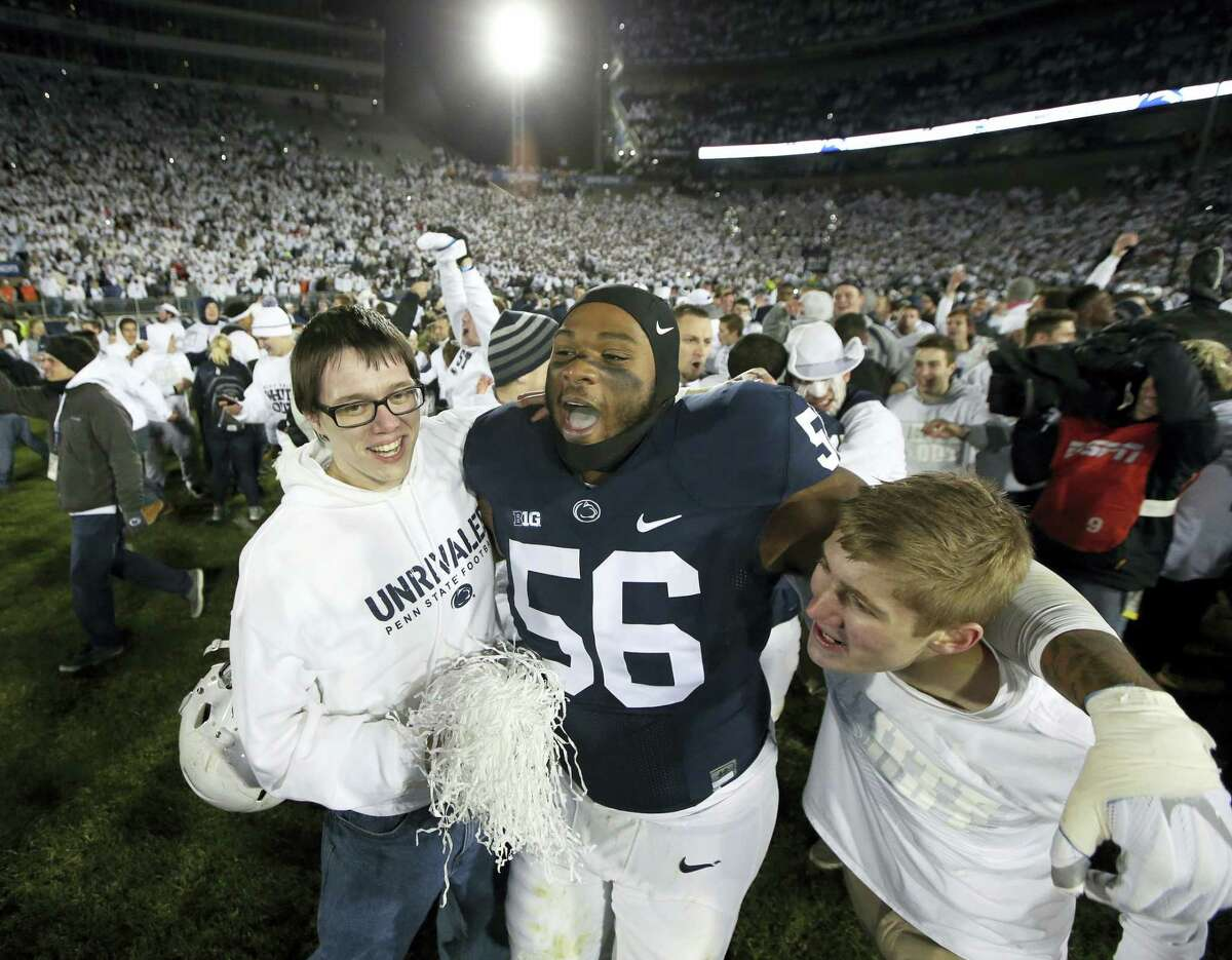 In this Oct. 22, 2016 photo, Penn State's Tyrell Chavis (56) celebrates with fans as they rush the field after Penn State upset Ohio State in an NCAA college football game in State College, Pa. A blocked field goal in the fourth quarter against Ohio State changed Penn State's season. The Nittany Lions have not lost since and Happy Valley is happier than it's been with its football team in the five years since a scandal shook the program and the school.