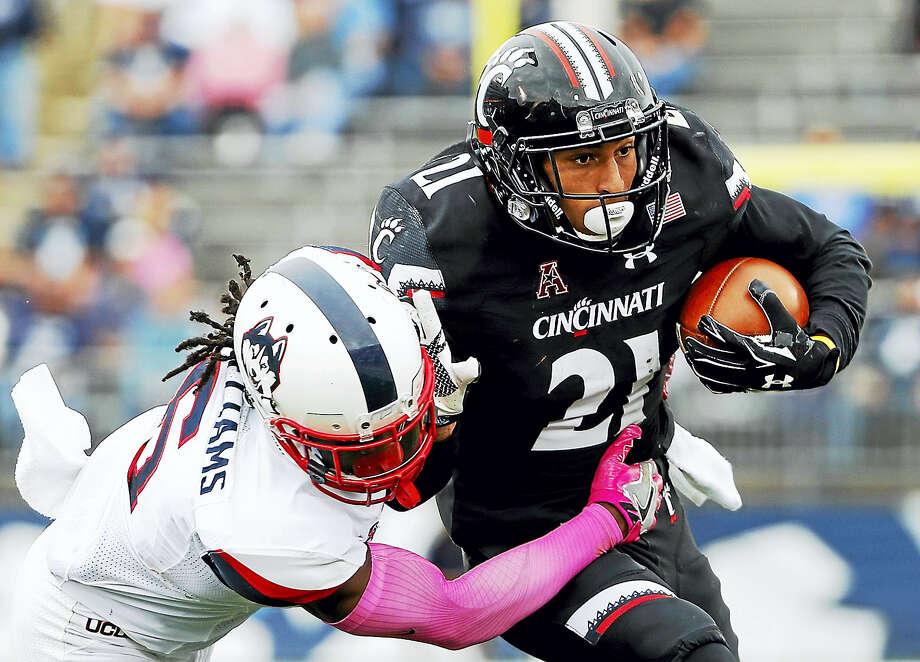 UConn's Jhavon Williams tackles Cincinnati wide receiver Devin Gray. Photo: The Associated Press File Photo  / FR170221 AP