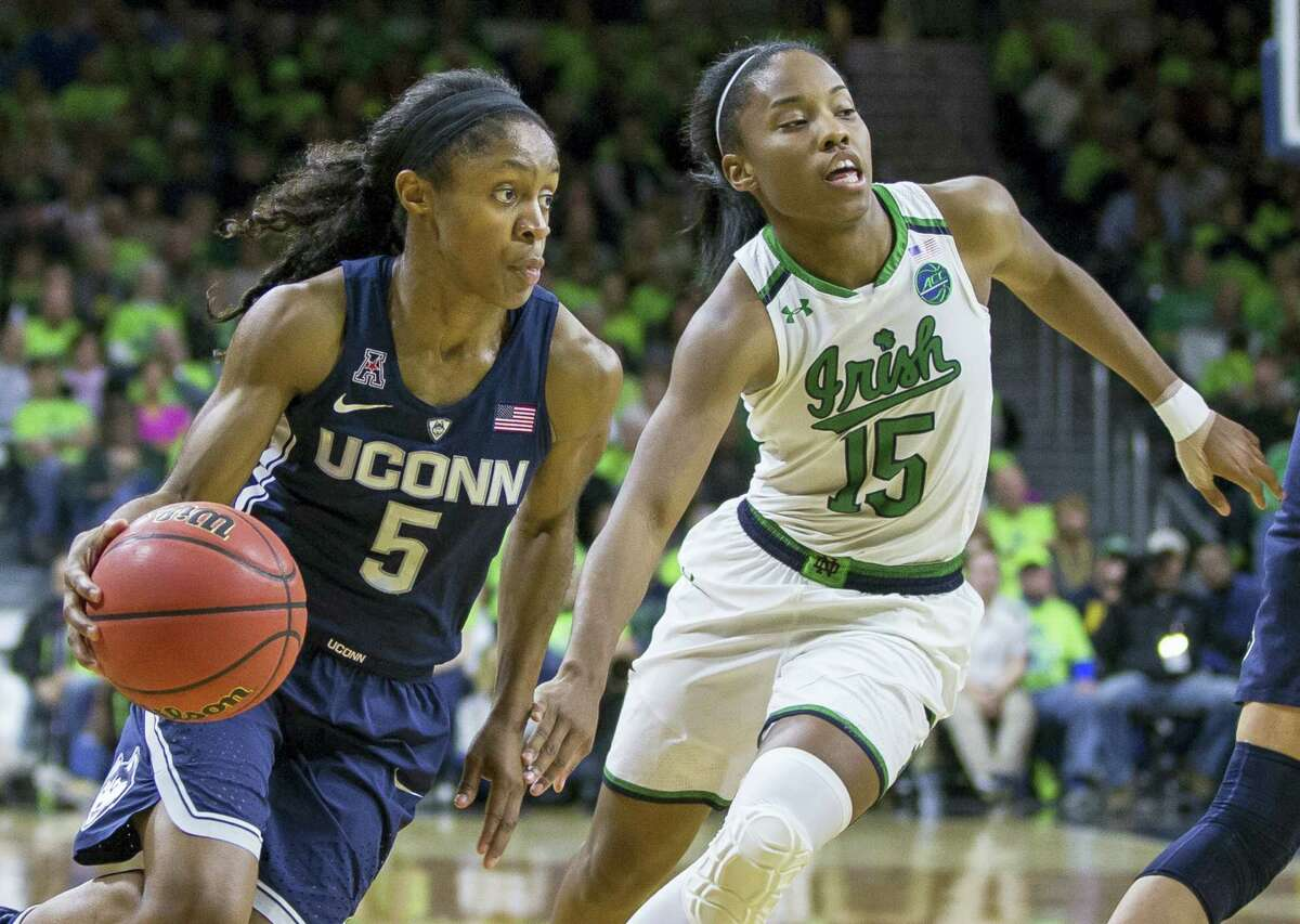 UConn's Crystal Dangerfield (5) drives by Notre Dame's Lindsay Allen during the second half of the Huskies' 83rd consecutive victory.