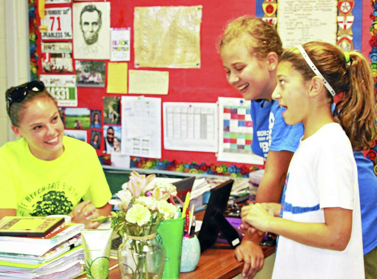 Independent Day School teacher Katy Carlebach of Middletown, left, laughs with two of her students. The avid runner was recently chosen as part of the Permanent Commission on the Status of Women's Young Women Rising Project.
