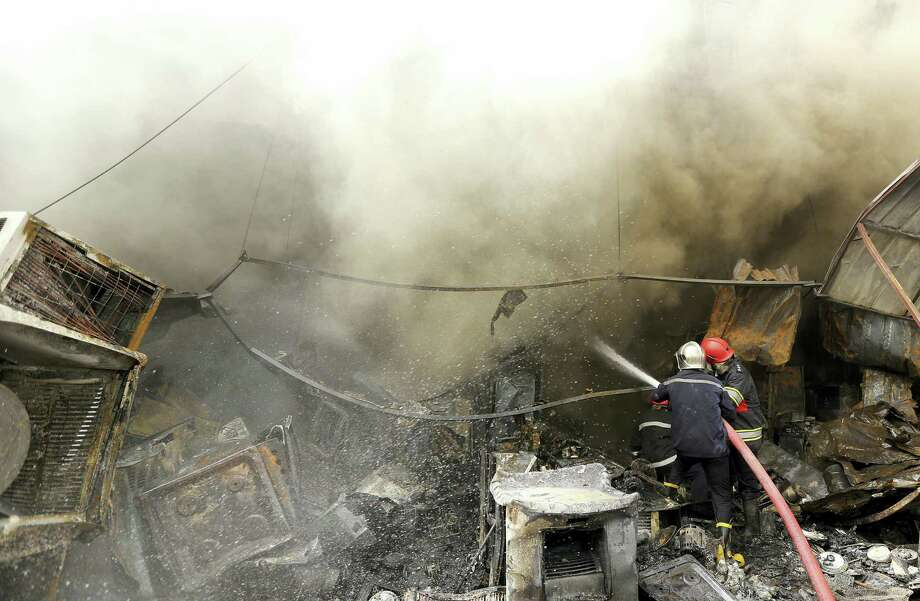 Firefighters work at the scene of a deadly suicide car bomb attack in the New Baghdad neighborhood of Baghdad, Iraq, Thursday, June 9, 2016. Two separate suicide attacks in and outside the Iraqi capital have killed at least 27 people and wounded dozens. Officials say the deadliest bombing took place in New Baghdad, a commercial area of a majority Shiite neighborhood in Baghdad, killing over a dozen civilians. Another suicide bomber rammed his explosives-laden car into an Iraqi army checkpoint north of Baghdad, killing at least 12 people. Photo: AP Photo/Hadi Mizban   / Copyright 2016 The Associated Press. All rights reserved. This material may not be published, broadcast, rewritten or redistribu