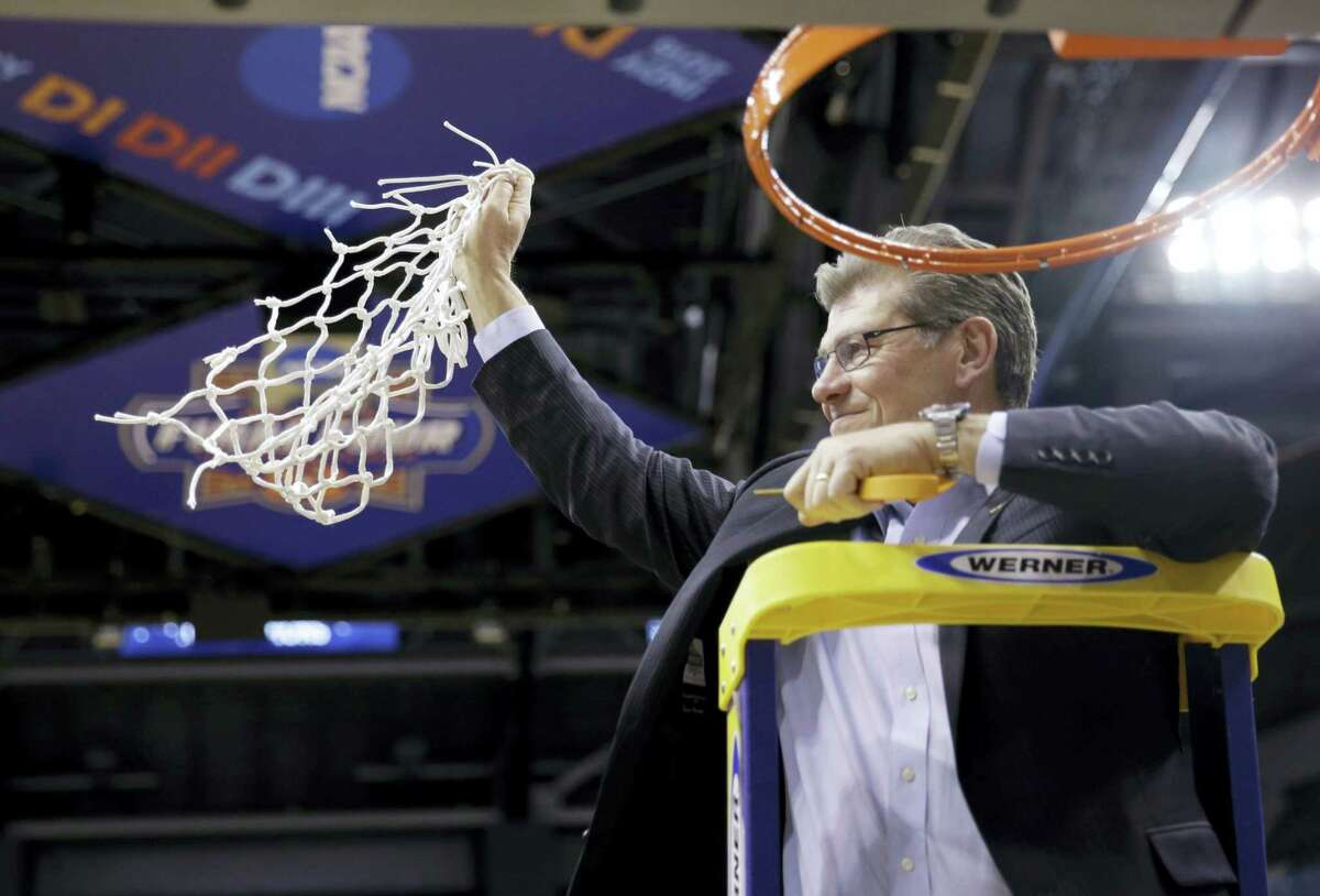 UConn head coach Geno Auriemmac celebrates by cutting down the net after Tuesday's game.