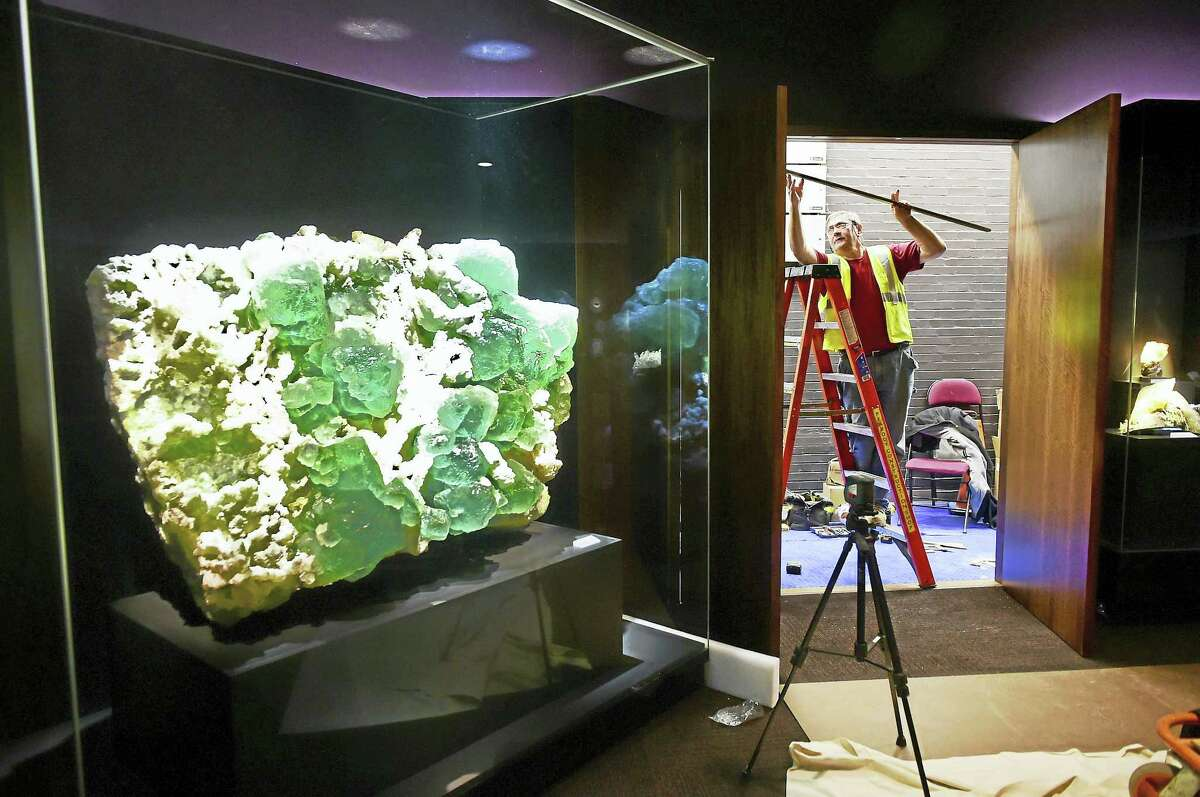 Carpenter Martin Belas adds some finishing touches to the construction of the Yale Peabody Museum of Natural History's new David Friend Hall. At left is a 4,000-pound lime-green fluorite with quartz.