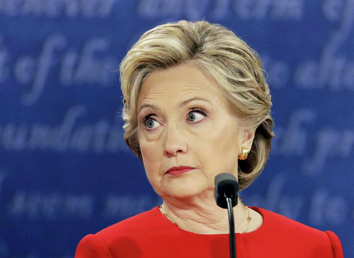 """FILE - In this Sept. 26, 2016 file photo, Democratic presidential nominee Hillary Clinton listens to Republican presidential nominee Donald Trump during the U.S. presidential debate at Hofstra University in Hempstead, N.Y. Clinton privately said the U.S. would """"ring China with missile defense"""" if the Chinese government failed to curb North Korea's nuclear program, a potential hint at how the former secretary of state would act if elected president. Clinton's remarks were revealed by WikiLeaks in a hack of the Clinton campaign chairman's personal account. (AP Photo/Julio Cortez, File)"""