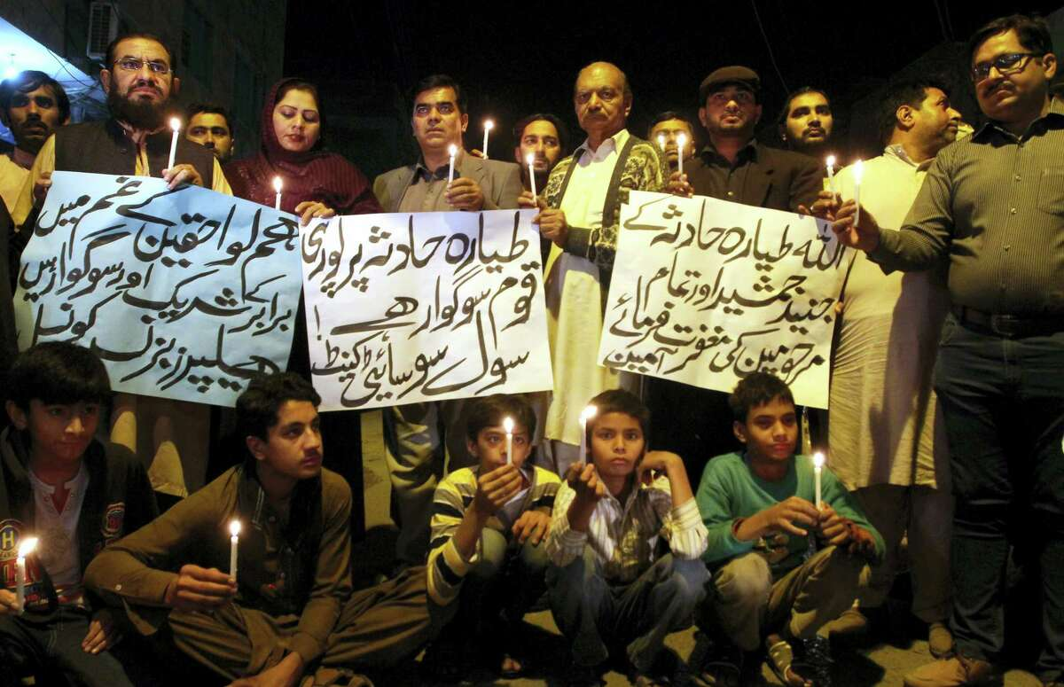 Members of a civil society group hold candles during a vigil for the victims of a plane crash, in Multan, Pakistan, Wednesday, Dec. 7, 2016. Pakistan's national carrier said the plane crashed shortly after takeoff from the northern city of Chitral with 48 people aboard. A spokesman for the Interior Ministry said there were no survivors. Rescuers told The Associated Press that the victims' bodies were beyond recognition.
