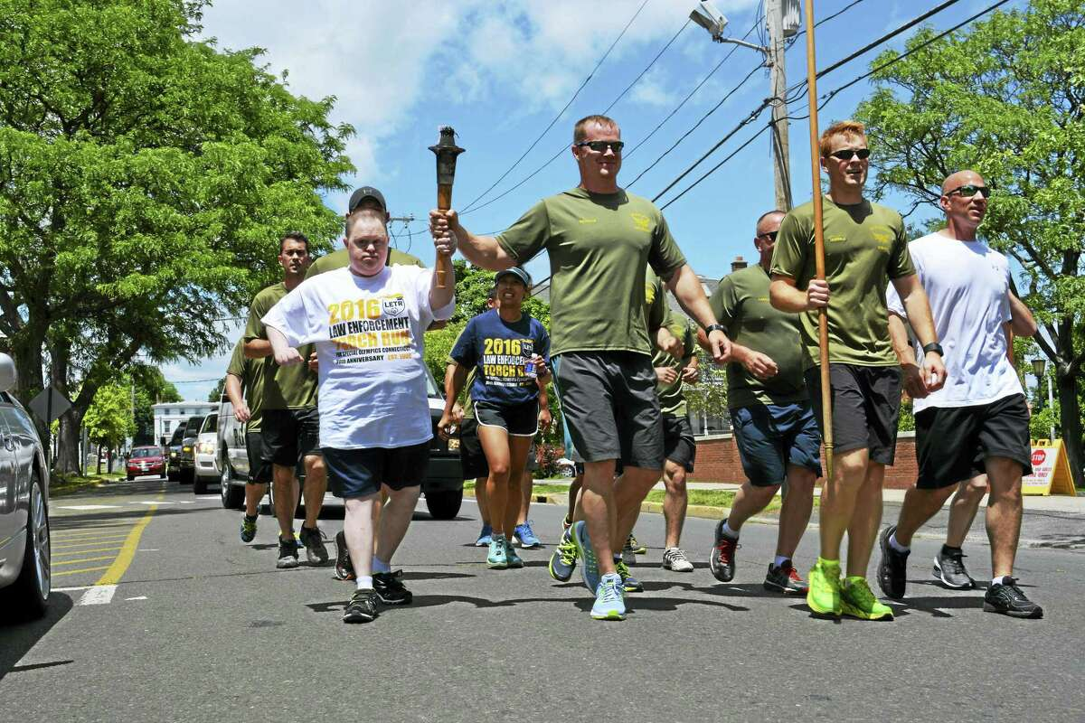Officers from Middletown, Meriden and other nearby towns ran the third leg of the Special Olympics Connecticut Law Enforcement Torch Run from Branford to Hartford Thursday. The eternal flame was passed to Special Olympics athlete Scott Maloney of Middletown in front of the Russell Library and he carried it to Middlesex Mutual where lunch awaited.