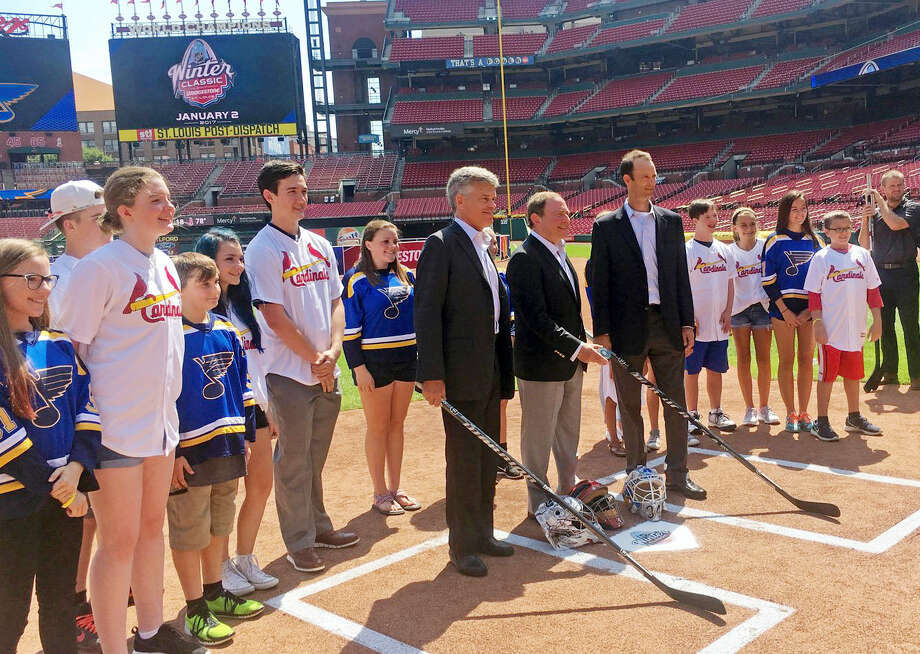 St. Louis Blues owner Tom Stillman, center left, NHL commissioner Gary Bettman, center, and St. Louis Cardinals president Bill DeWitt III, center right, pose at Busch Stadium's home plate with hockey sticks during a press conference for the NHL Winter Classic Tuesday in St. Louis. The baseball stadium will host an outdoor hockey game between the Blues and the Chicago Blackhawks. Photo: Jeremy Rutherford — St. Louis Post-Dispatch Via AP  / St. Louis Post-Dispatch
