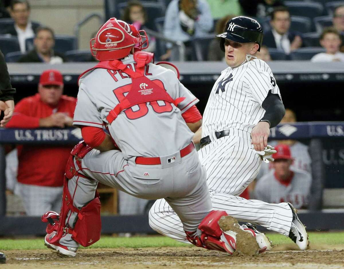 FRANK FRANKLIN II — THE ASSOCIATED PRESS New York Yankees' Johnny Barbato slides past Los Angeles Angels catcher Carlos Perez to score on a Brett Gardner single during the fourth inning of the Yankees' 12-6 victory Wednesday.