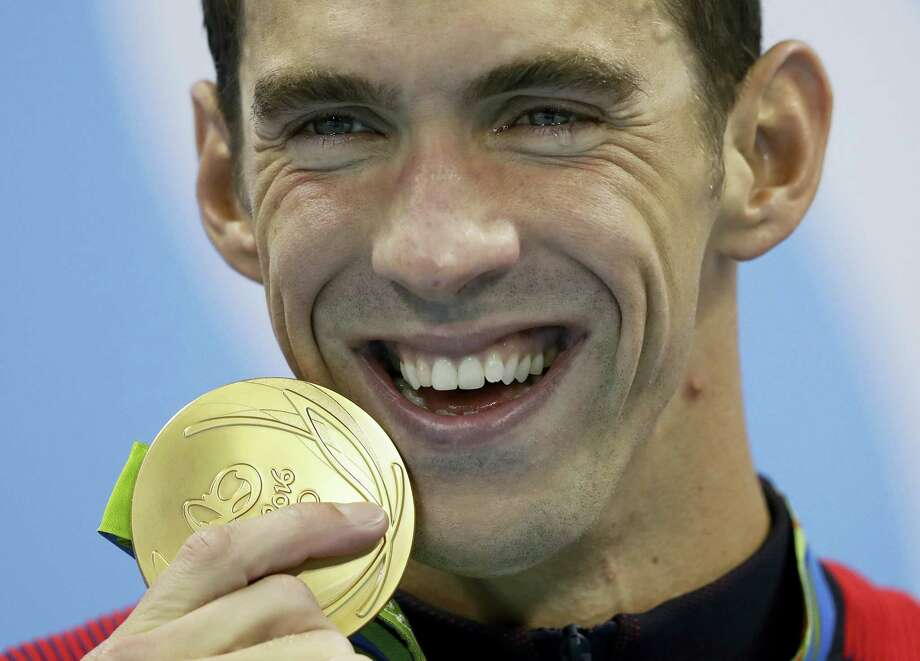 Michael Phelps shows off his gold medal after winning the men's 200-meter butterfly on Tuesday. Photo: Michael Sohn — The Associated Press  / Copyright 2016 The Associated Press. All rights reserved. This material may not be published, broadcast, rewritten or redistribu