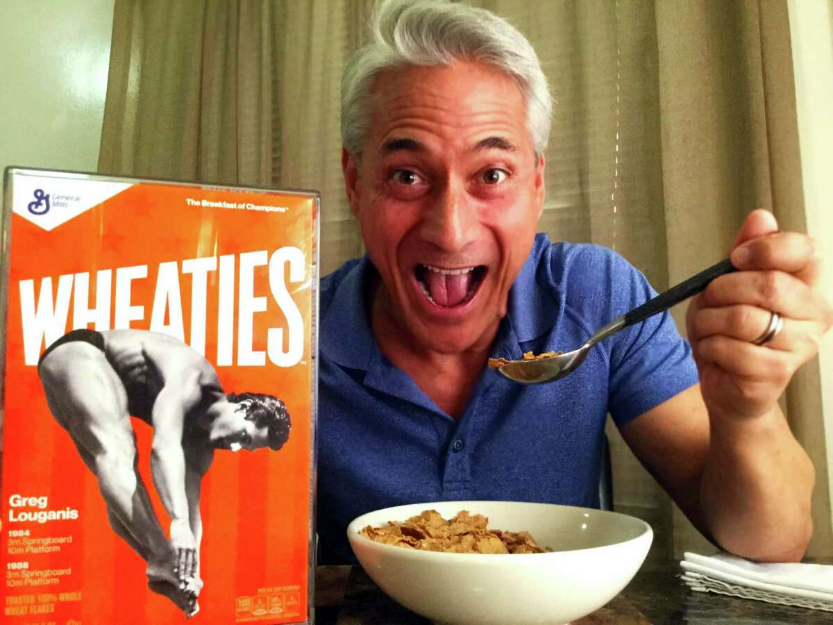 This image released by CW3PR shows former Olympic diver Greg Louganis posing with Wheaties cereal next to a commemorative box featuring him on the cover at his home on Tuesday.