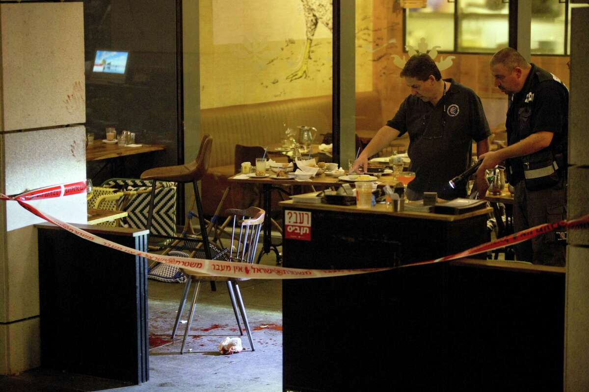 Israeli police officers examine the scene of a shooting attack in Tel Aviv, Israel, Wednesday, June 8, 2016. Two Palestinian gunmen opened fire in central Tel Aviv Wednesday night, killing three people and wounding at least five others, Israel police said.