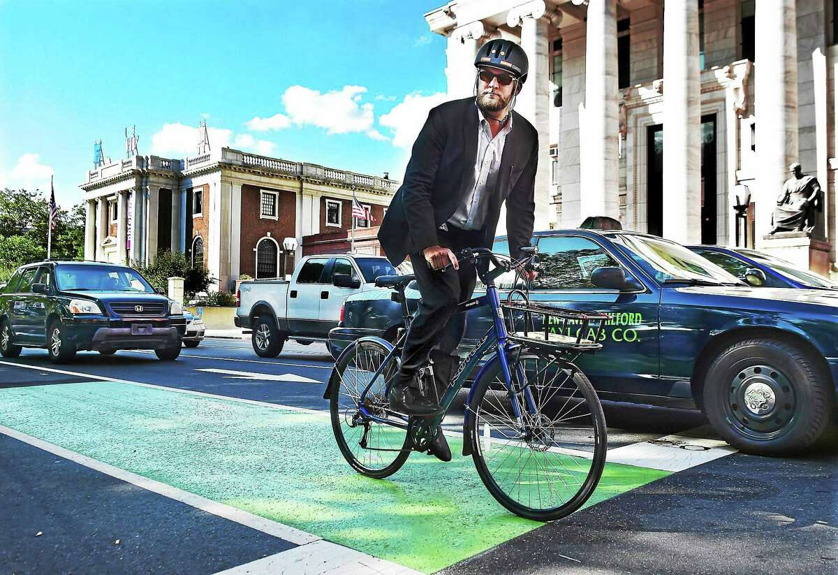 Doug Hausladen, the director of Transportation, Traffic & Parking for the city of New Haven travels Elm Street by bike on a city designated path. Hausladen bikes or walks to work daily.