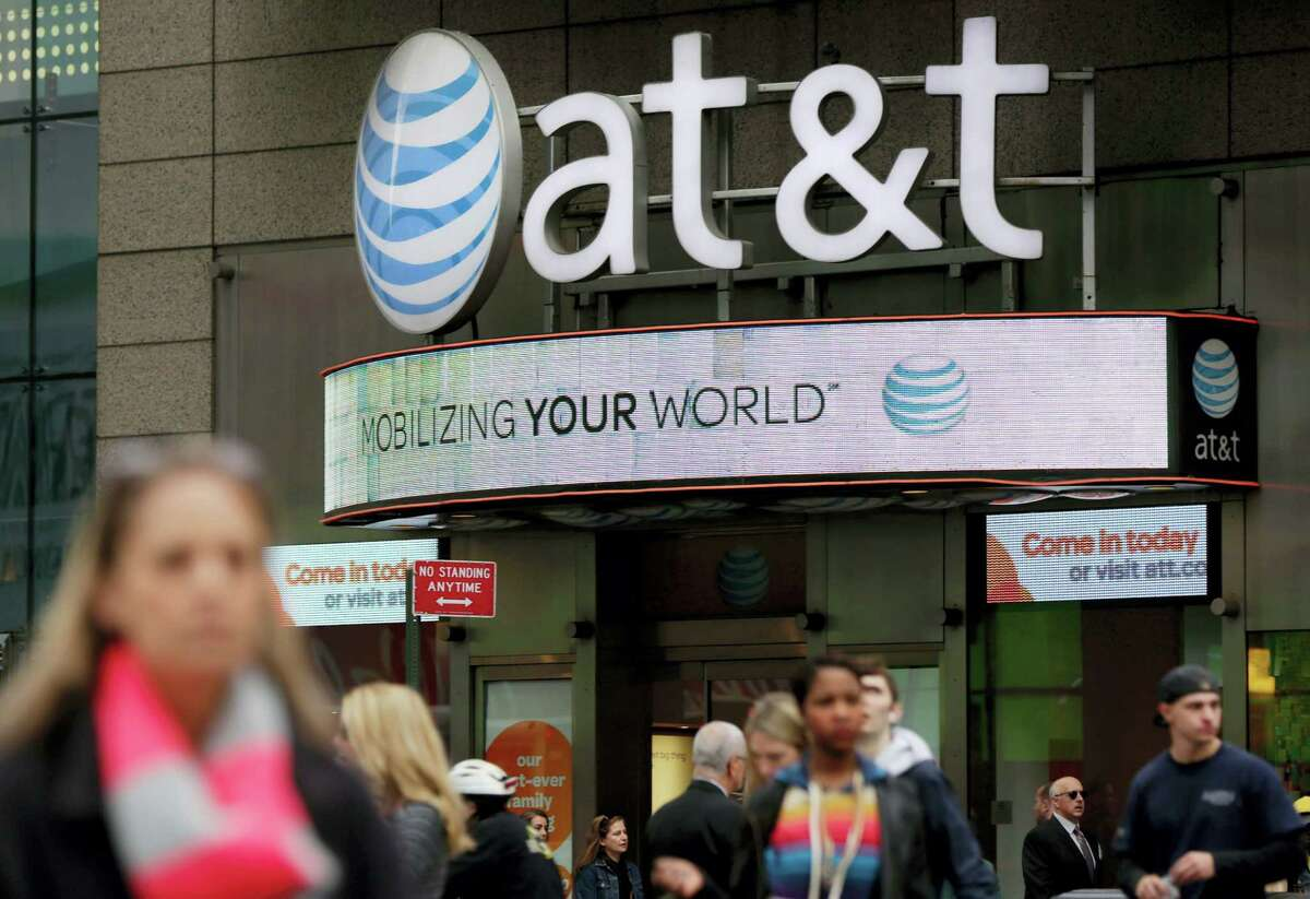 People pass an AT&T store in New York's Times Square.