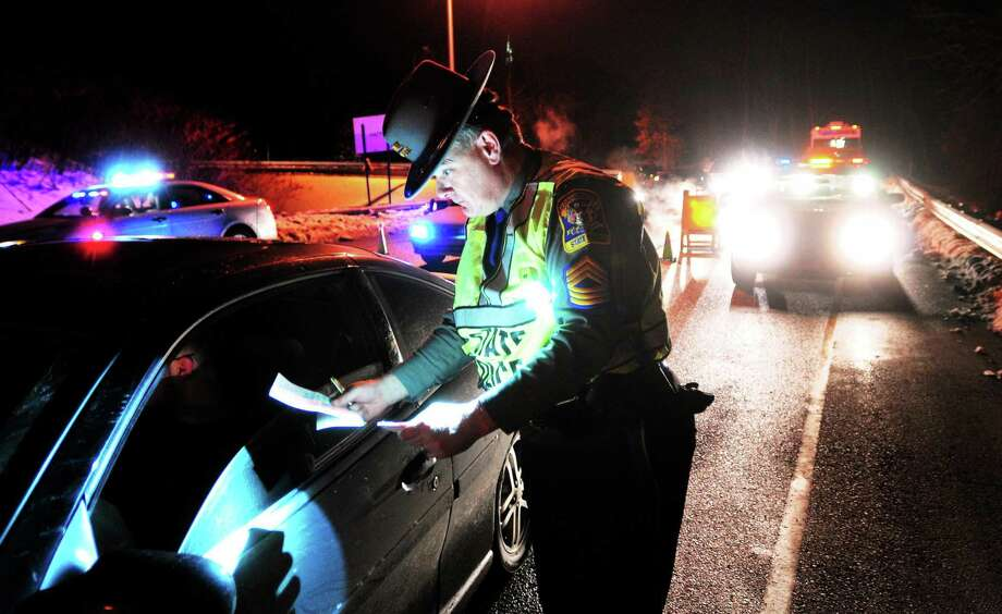 An officer cites a driver for illegally tinted windows at a sobriety checkpoint in this archive photograph. Photo: File