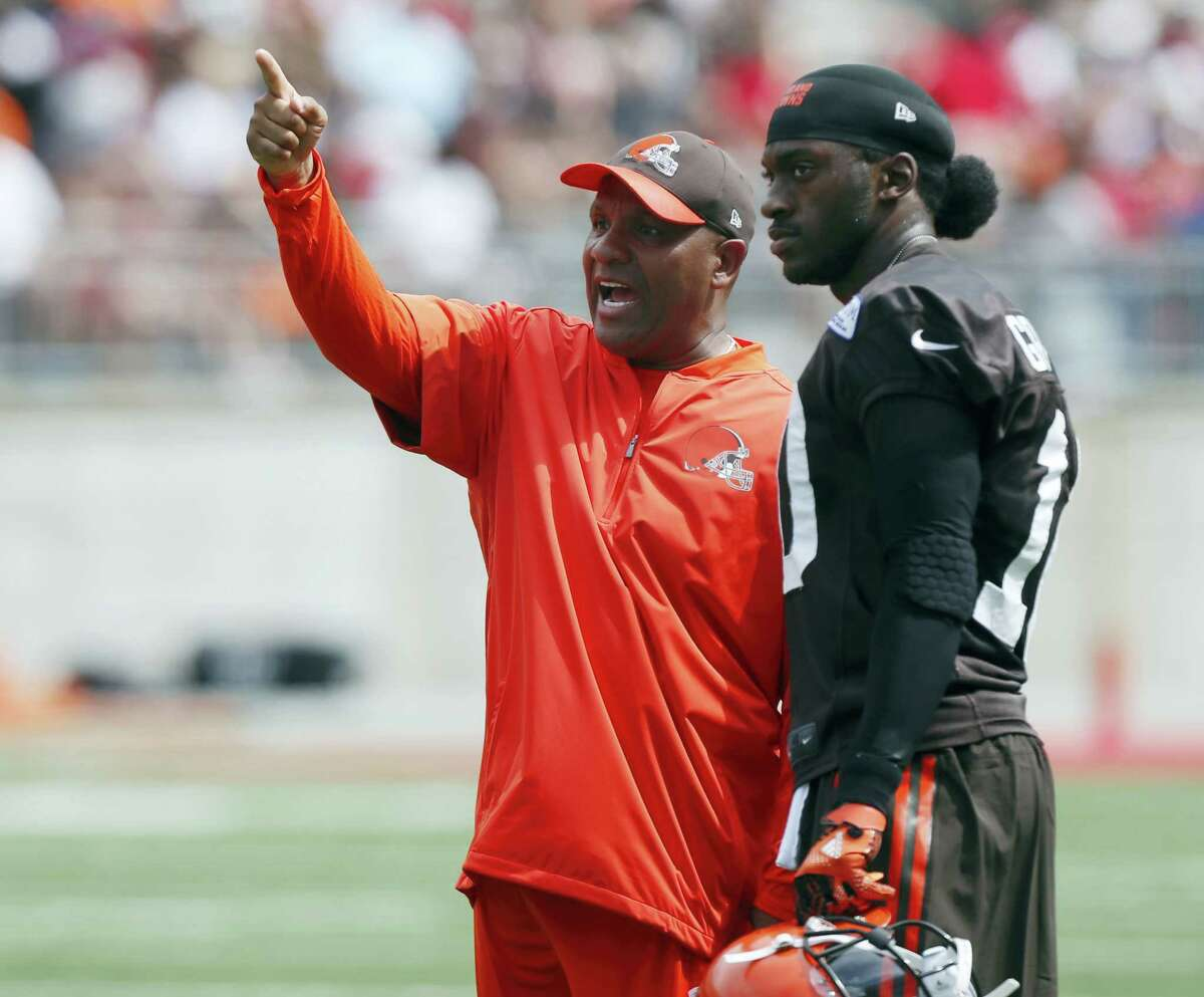 Cleveland Browns head coach Hue Jackson, left, talks with quarterback Robert Griffin III during their orange and brown scrimmage at the NFL football team's training camp on Aug. 6, 2016 in Columbus, Ohio.