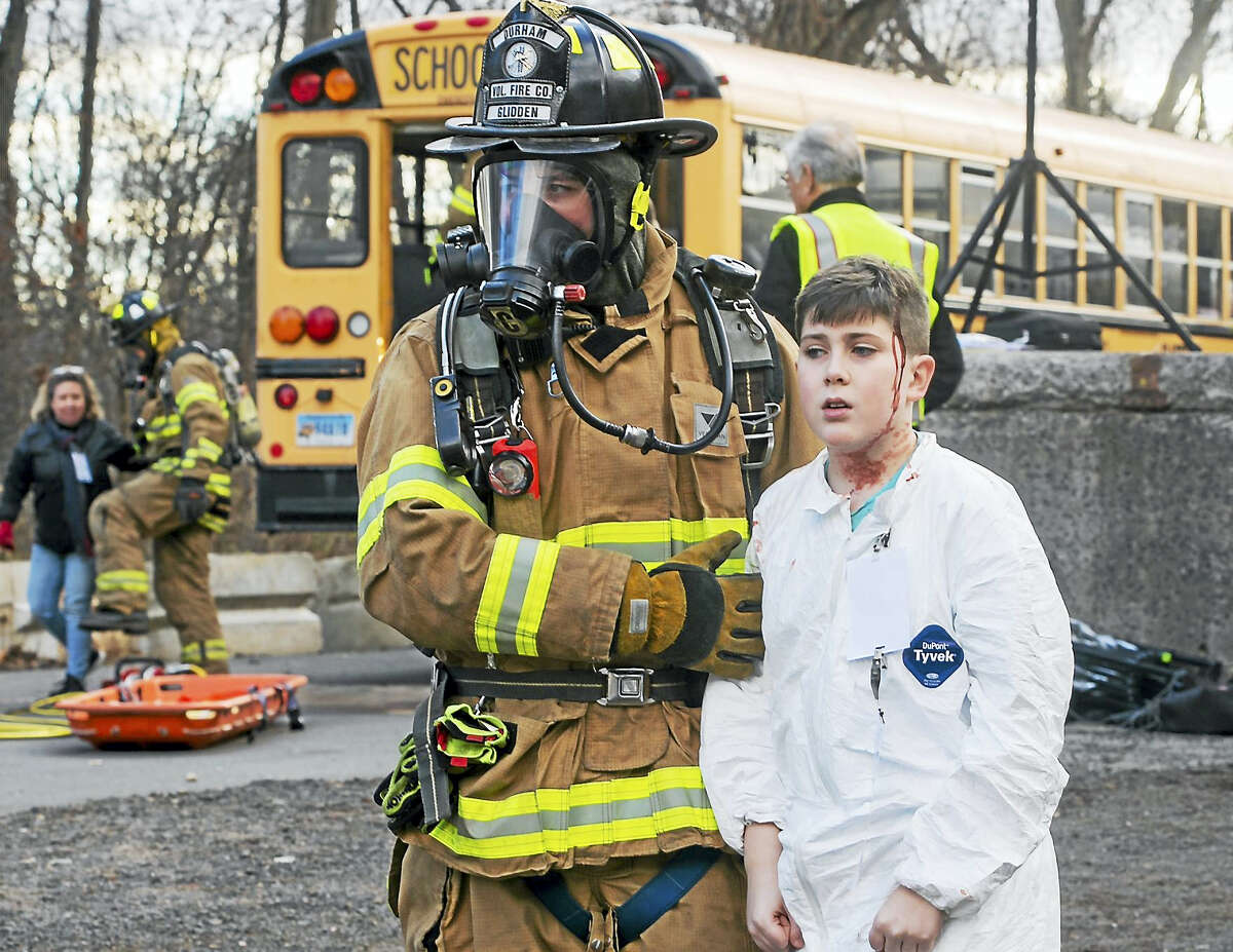 """A student """"injured"""" in a school bus accident is carried to safety during the regional emergency response drill Saturday in Middlefield."""