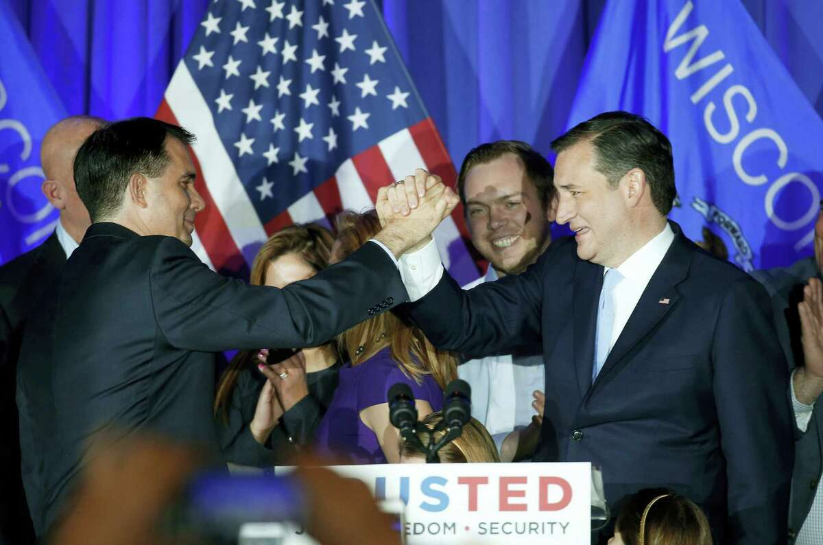 Republican presidential candidate Sen. Ted Cruz, R-Texas, right, clasps hands with Wisconsin Gov. Scott Walker, left, during a primary night campaign event, Tuesday, April 5, 2016, in Milwaukee, Wisc.