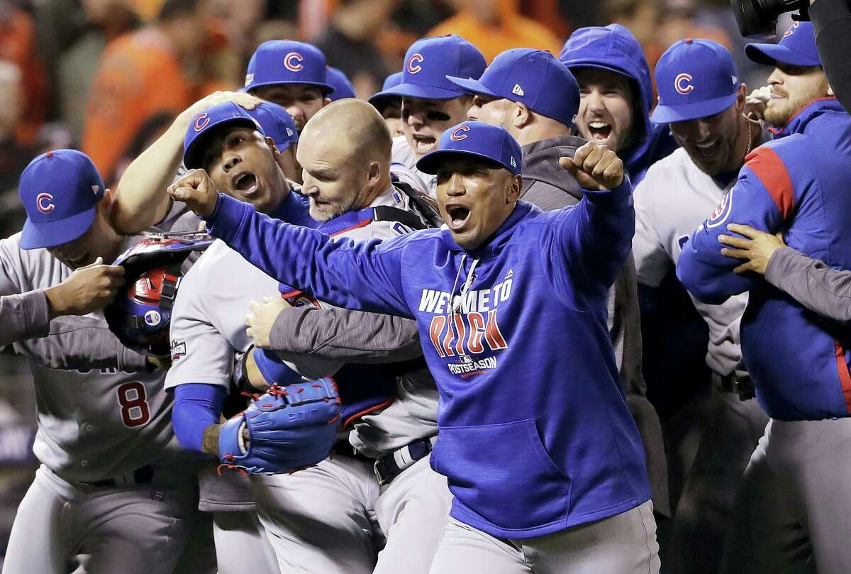 Chicago Cubs pitcher Aroldis Chapman, second from left, catcher David Ross, third from left, and teammates celebrate after Game 4 of baseball's National League Division Series against the San Francisco Giants in San Francisco, Tuesday. The Cubs rallied in the ninth inning for a 6-5 win.