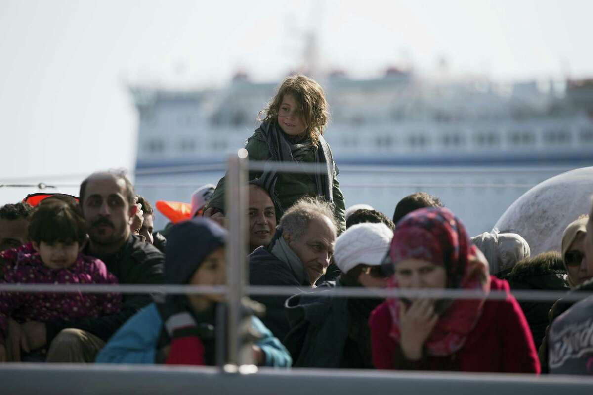 Refugees and migrants arrive in the port of Mytilini on a Greek navy vessel after a rescue operation in the Aegean sea near the shores of Lesbos island on April 4, 2016 during the first day of the implementation of the deal between EU and Turkey.