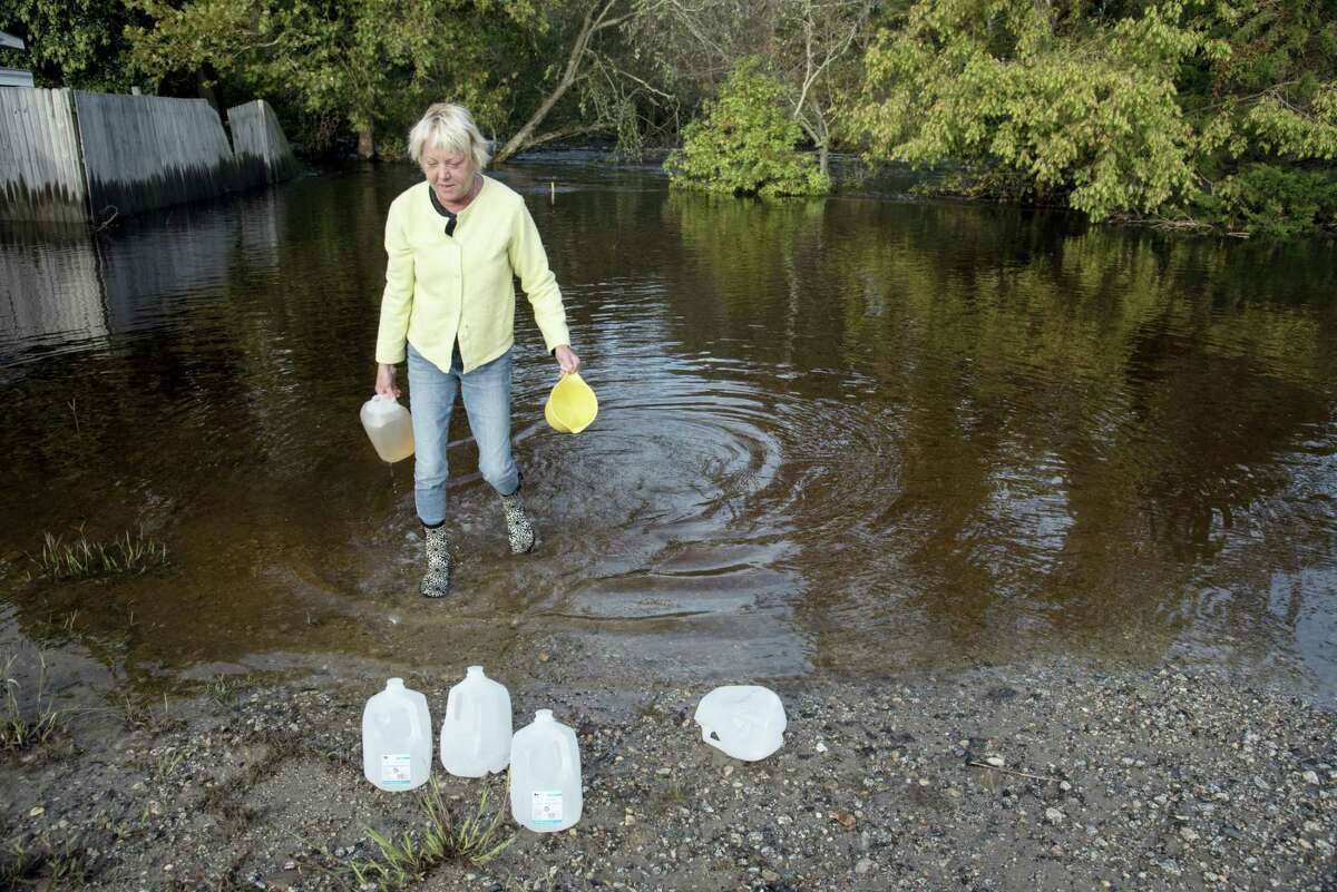 Caroline Kahn collects gallon jugs of water at the foot of 3rd Street in Lumberton, N.C., from floodwaters caused by rain from Hurricane Matthew to use for their plumbing needs Wednesday, Oct. 12, 2016. In North Carolina, tens of thousands of people, some of them as much as 125 miles inland, have been warned to move to higher ground since the hurricane drenched the state.