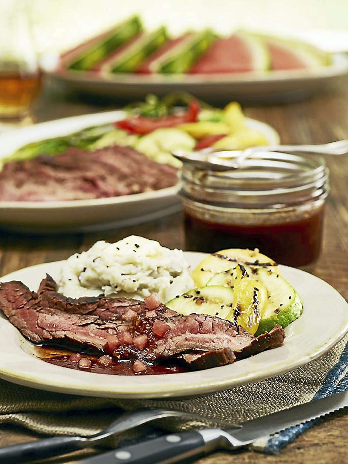 Flank steak with watermelon bourbon glaze pairs well with mashed potatoes and grilled vegetables.
