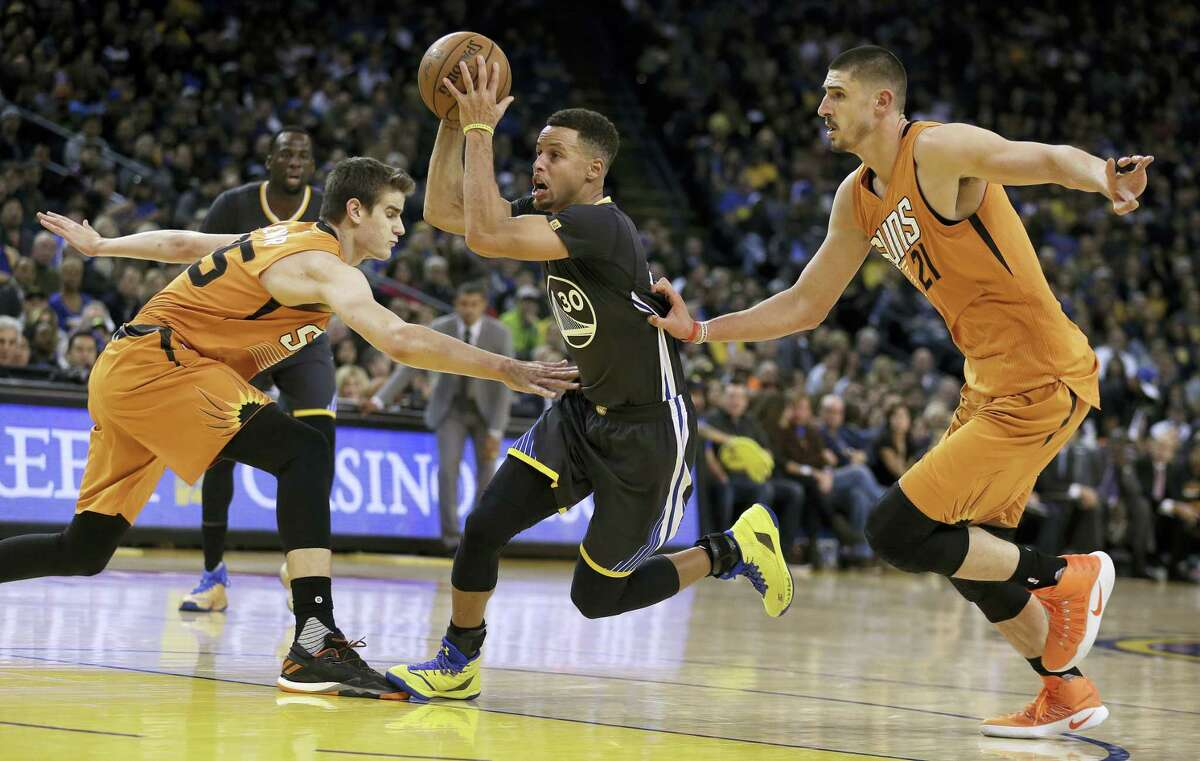 Golden State Warriors' Stephen Curry, center, drives between Phoenix Suns' Dragan Bender, left, and Alex Len during the second half of an NBA basketball game Saturday, Dec. 3, 2016 in Oakland, Calif.