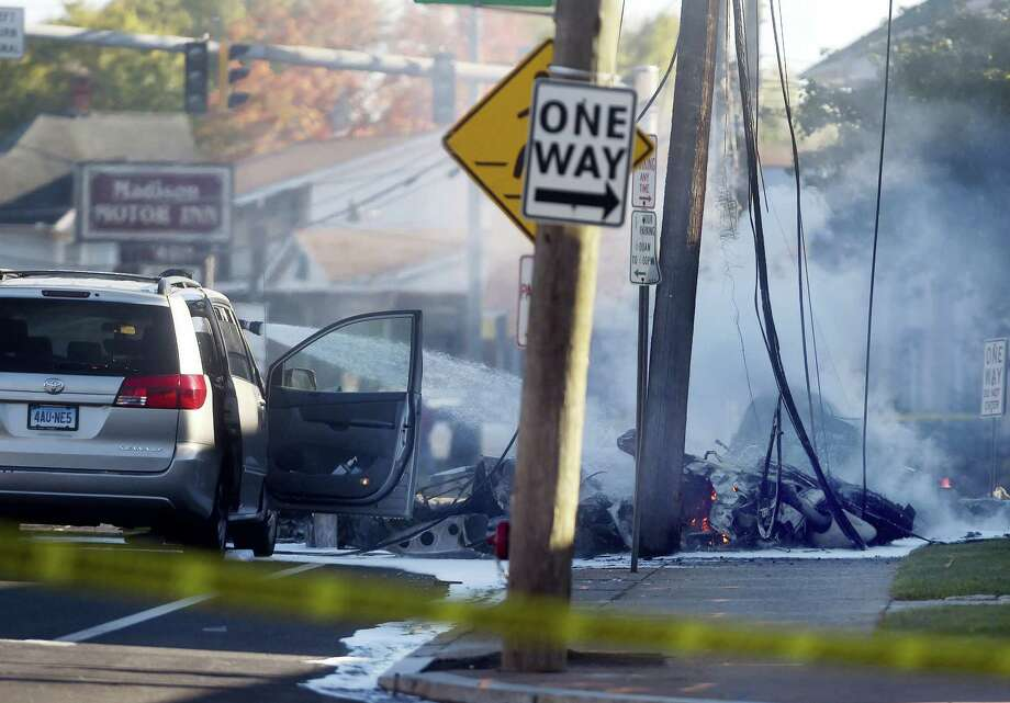 Smoke pours from the smoldering remains of a small plane that crashed on Main Street in East Hartford, Conn. on Oct. 11, 2016. Authorities said at least one person is dead and another is injured after a small airplane crashed near the Connecticut River. Photo: Jim Michaud/Journal Inquirer Via AP  / Journal Inquirer