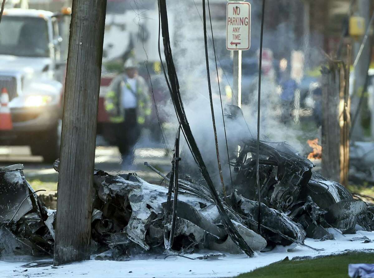 Smoke pours from the smoldering remains of a small plane that crashed on Main Street in East Hartford, Conn. on Oct. 11, 2016. Authorities said at least one person is dead and another is injured after a small airplane crashed near the Connecticut River.
