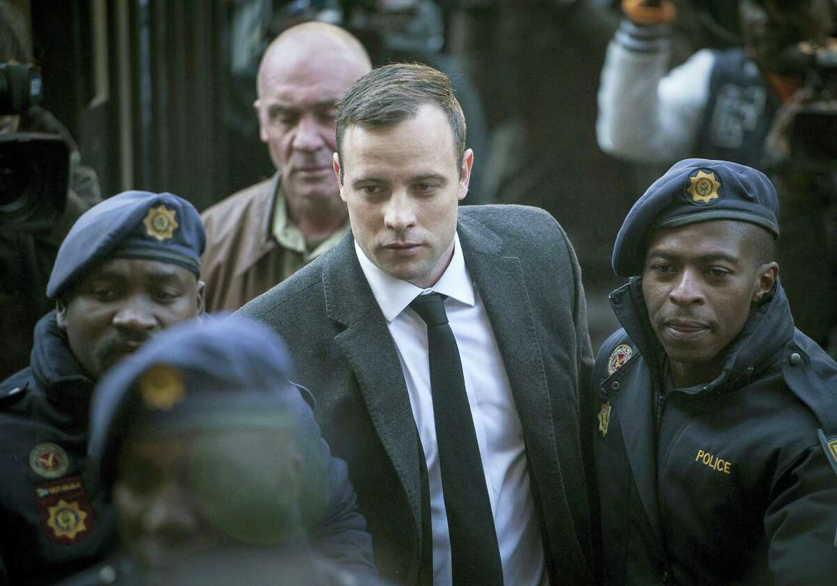 In this July 6, 2016 photo, Oscar Pistorius, center, arrives at the High Court in Pretoria, South Africa, for a sentencing hearing for the murder of his girlfriend Reeva Steenkamp in his home on Valentine's Day 2013. South African prison officials said on Aug. 7, 2016 that Pistorius was treated for injuries at a private hospital and has returned to a jail where he is serving a six-year sentence.