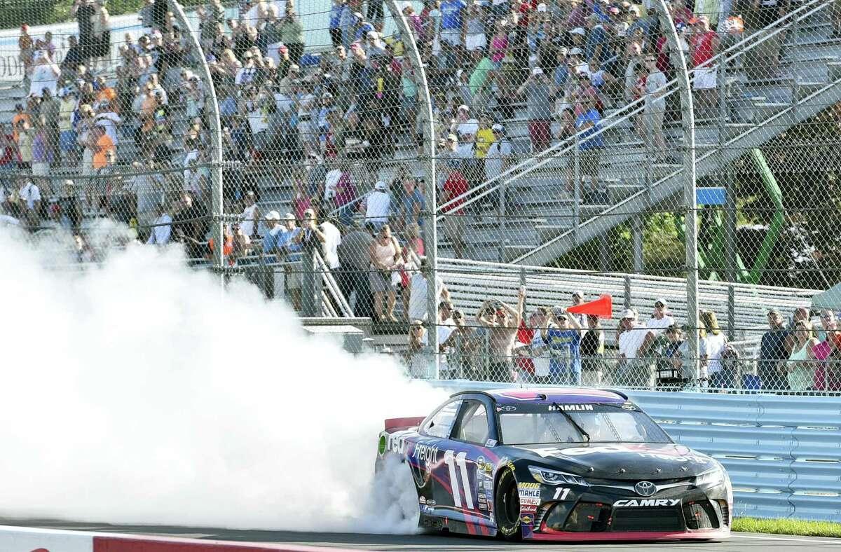 Denny Hamlin celebrates with a burnout after winning at Watkins Glen International on Sunday in Watkins Glen, N.Y.