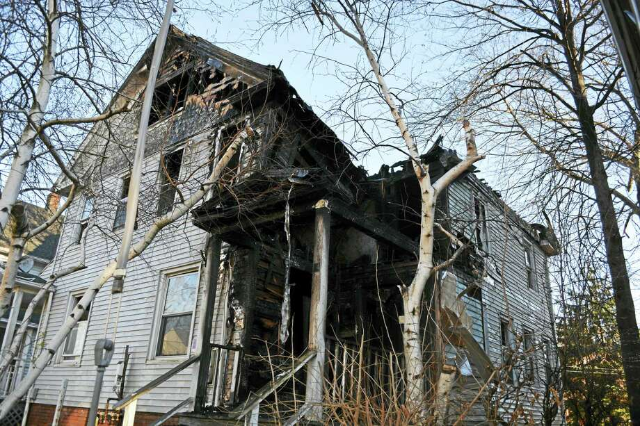 A blaze that touched off early Sunday at 14 Glover Place in Middletown left the home and the one next door condemned. Photo: Cassandra Day — The Middletown Press