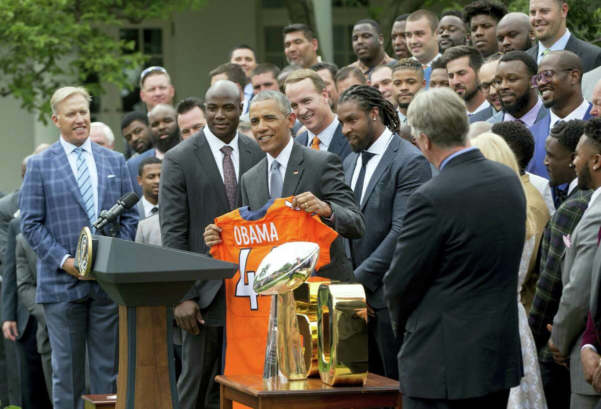 President Barack Obama holds up a Broncos jersey, as he welcomes the Super Bowl Champions during a ceremony in the Rose Garden of the White House in Washington on Monday.