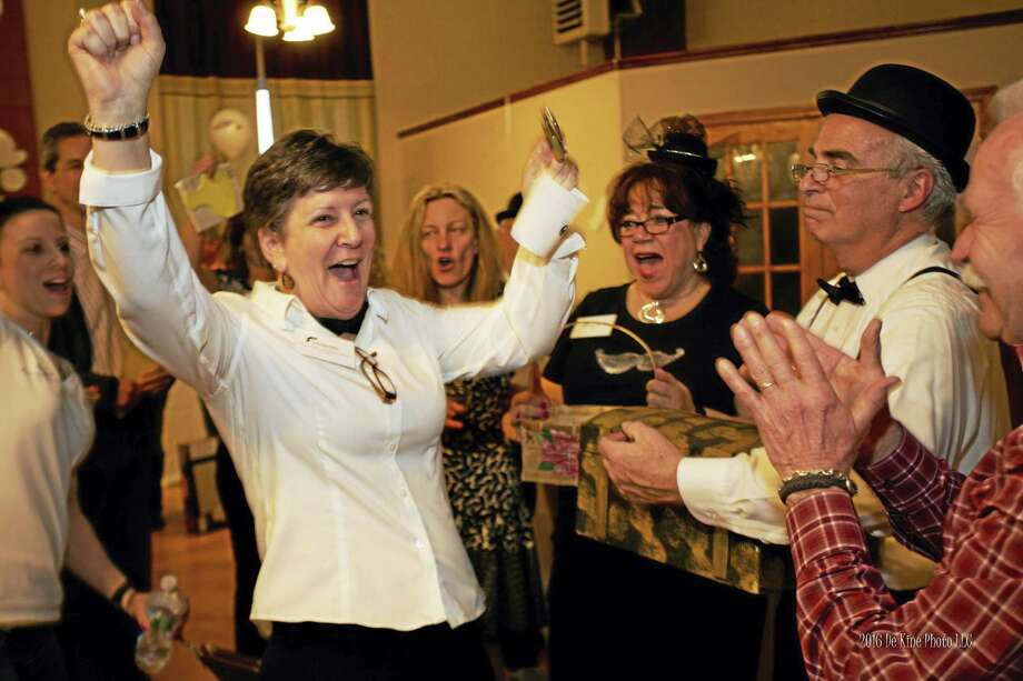 The Middlesex County Chamber of Commerce held its Business After Work Auction & Taste of Downtown on March 29 at the Italian Society in Middletown. This year's winning raffle prize was an overnight stay at the Inn at Middletown with breakfast and a gift certificate to Illiano's; a prize valued at $350. From left are treasure chest winner Sharon Graves; looking on is Marie Leavitt, event chairman Al Santostefano and auctioneer Bill Barrows. Photo: De Kine Photo LLC   / (c)DE KINE PHOTO LLC