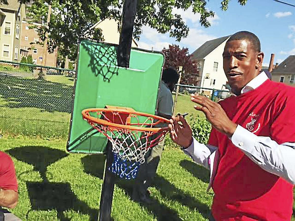 "UConn men's basketball coach Kevin Ollie helps put up a net on a rim at ""Kevin's Kourt"" in Hartford on Monday."