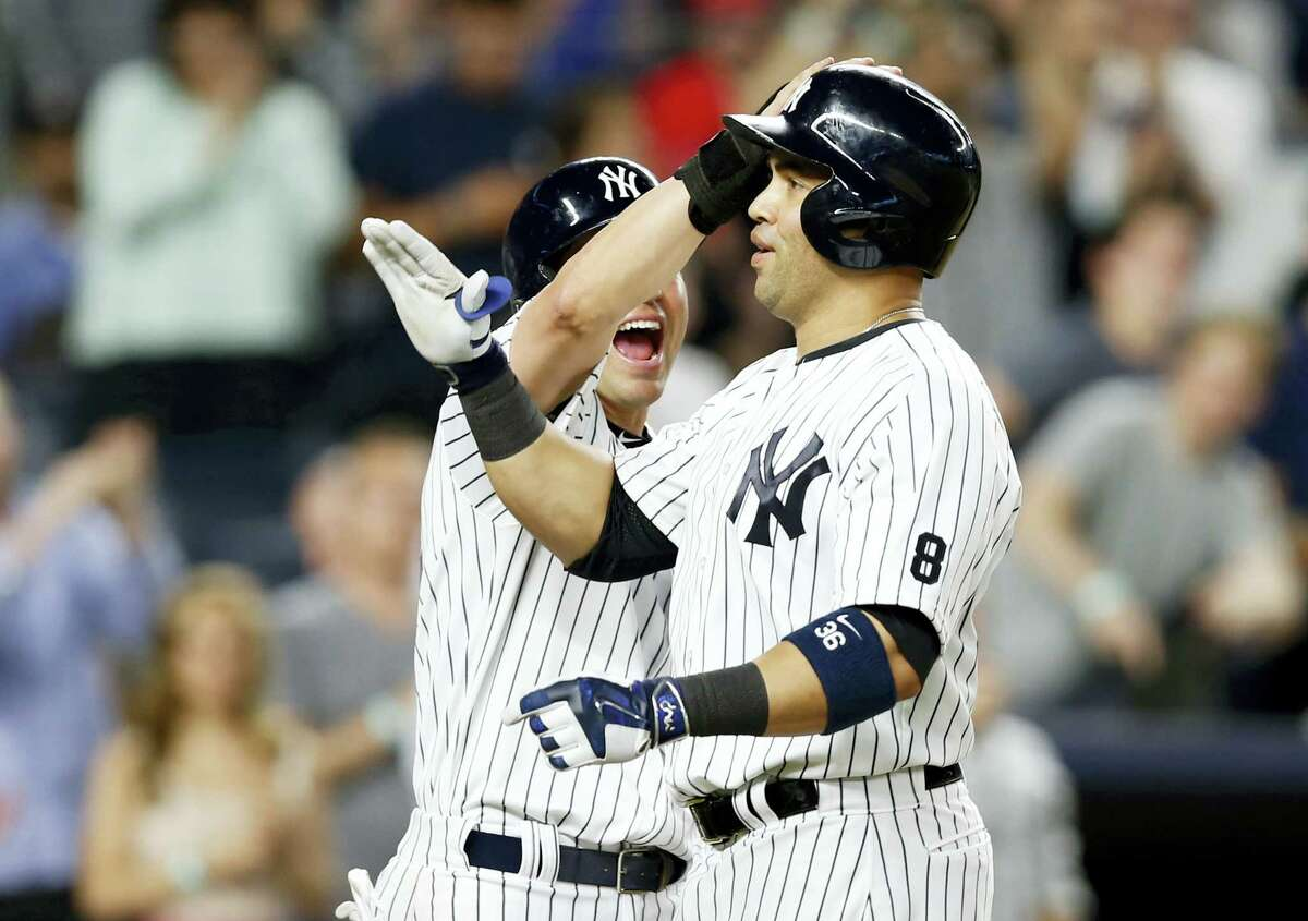 Jacoby Ellsbury, left, celebrates with teammate Carlos Beltran after scoring on Beltran's three-run home run in the eighth inning on Monday.