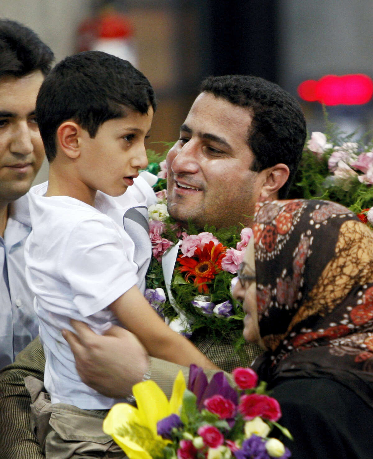 In this July 15, 2010 photo, Shahram Amiri, an Iranian nuclear scientist greets his son Amir Hossein as he arrives to the Imam Khomeini airport after returning from the United States, outside Tehran, Iran. Amiri, who was caught up in a real-life U.S. spy mystery and later returned to his homeland and disappeared, has reportedly been executed under similarly mysterious circumstances.