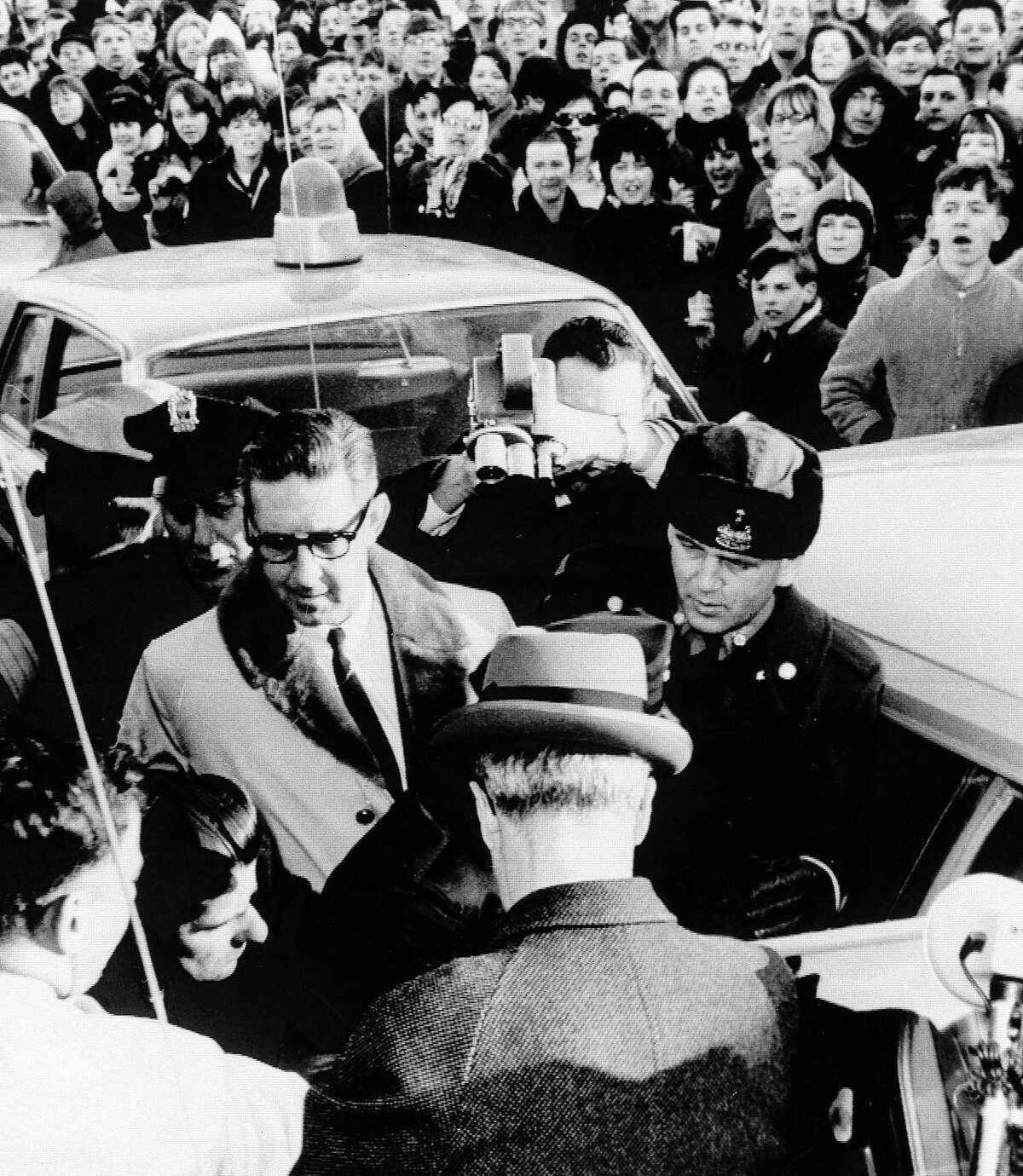 In this Feb. 26, 1967 black and white photo, the crowd jeers self-confessed Boston Strangler Albert DeSalvo, lower left, as he is led outside the Lynn, Mass. police station. Casting is underway in summer 2016 for 'Stranglehold,' a new movie that will focus in part on a man who claimed psychic powers who helped investigators search for clues for nearly a dozen unsolved murders of women in the 1960s.