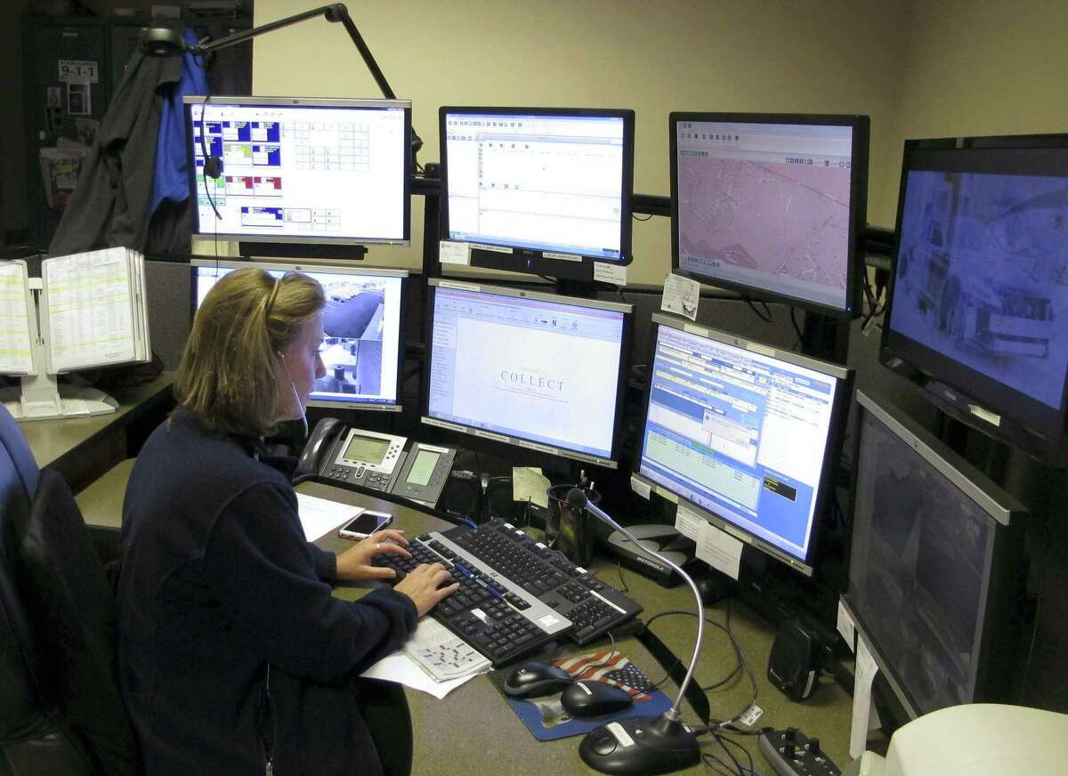 Dispatcher Kelly Orsini works at her communications desk at the police department in Naugatuck. Some police chiefs have said their officers may not be able to communicate on encrypted systems with first-responders in neighboring towns.