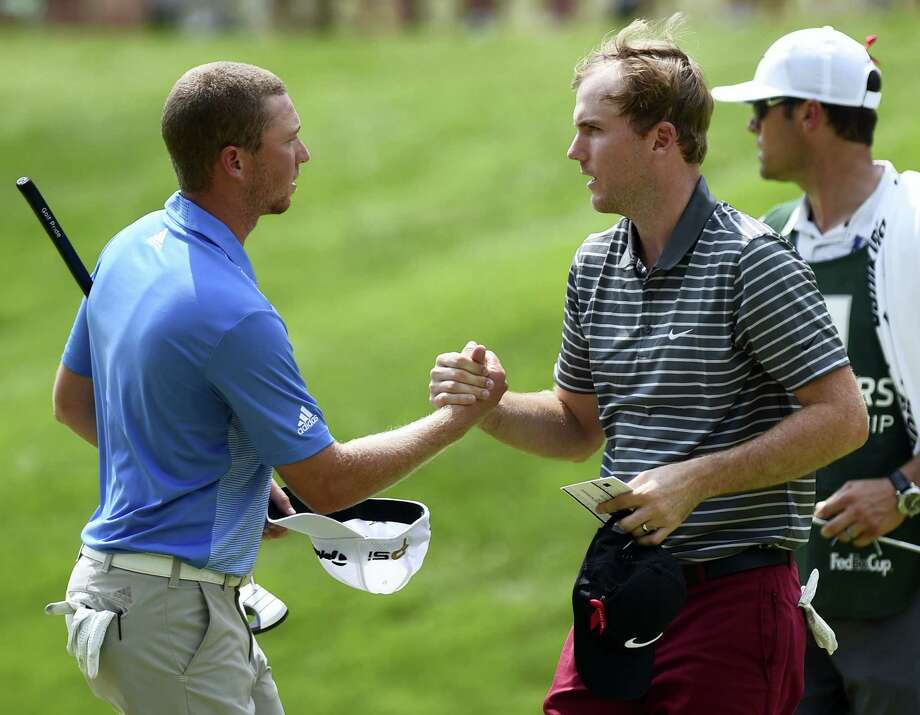 Tournament leader Daniel Berger, left, and Russell Henley shake hands after completing the third round at the Travelers on Saturday. Photo: Brad Horrigan — Hartford Courant Via AP  / Hartford Courant