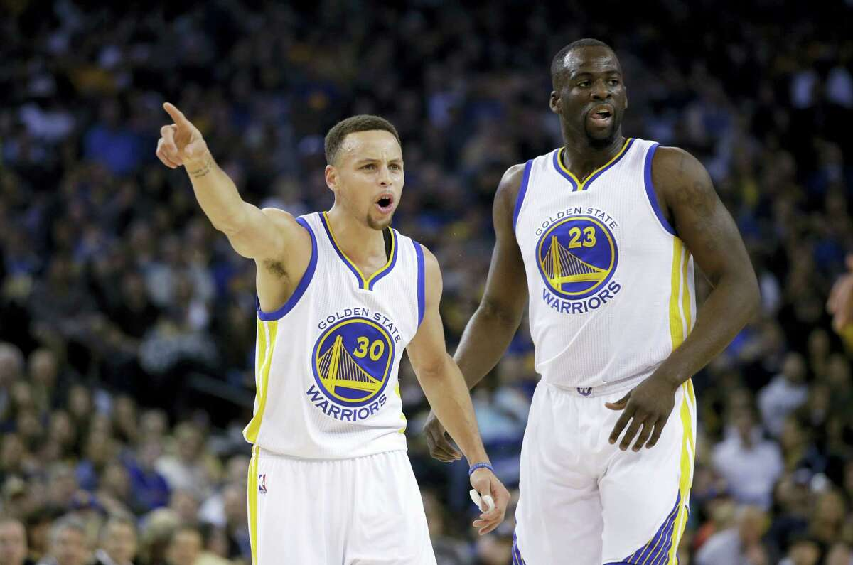 The Warriors' Stephen Curry (30) argues a call next to teammate Draymond Green during the first half on Friday night.
