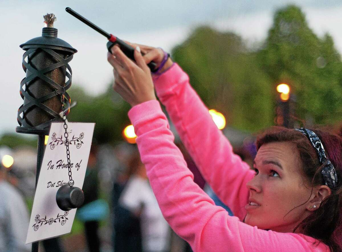 Mallory, of Middletown, lights a candle in honor of Dot Sherman at the Greater Middletown Relay for Life at Woodrow Wilson Middle School in 2014.