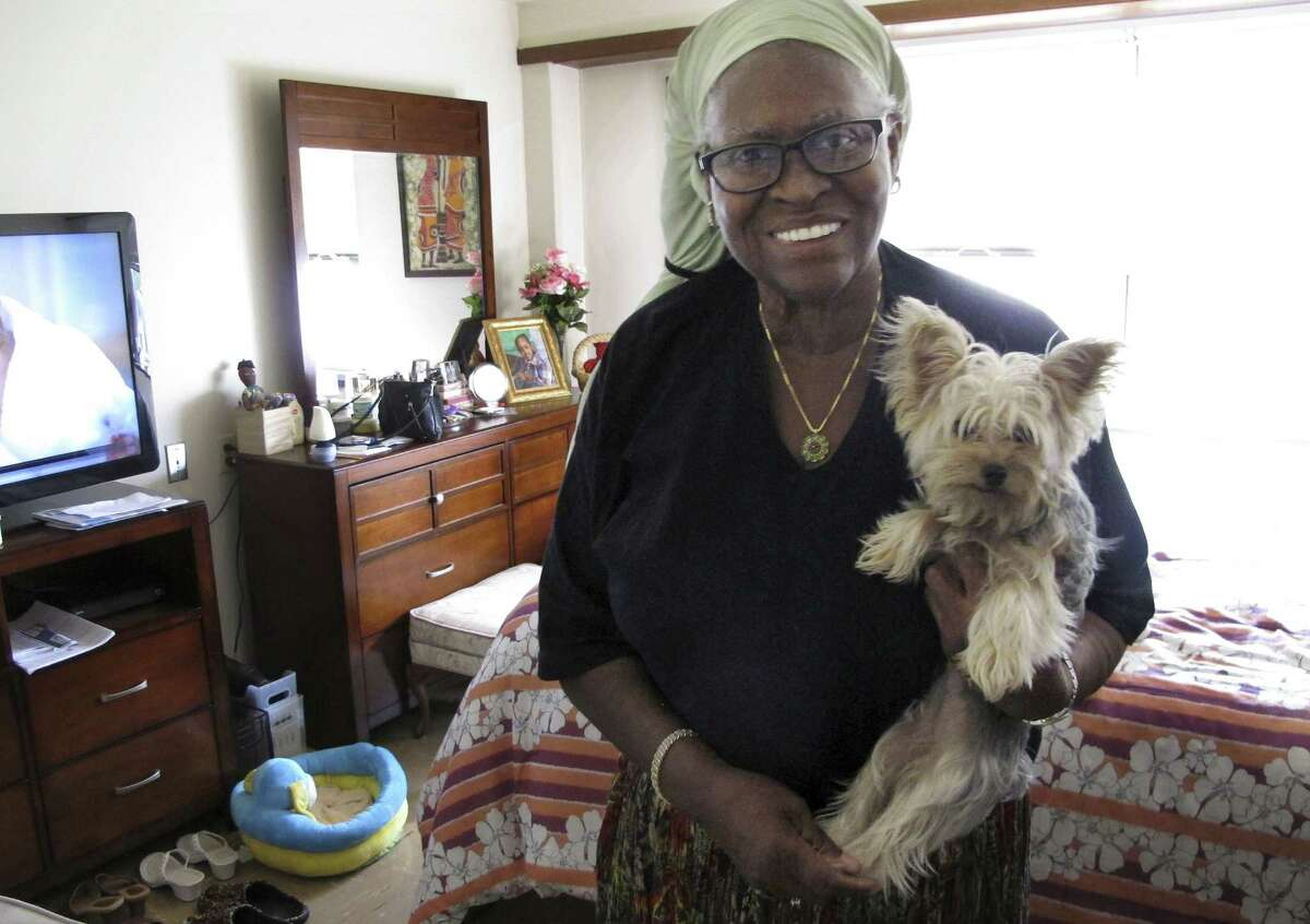 In this Aug. 25, 2015, photo, Bonnie Jean Cook holds her therapy dog, Bella, in her apartment in East Hartford, Conn. Cook, 68, is adjusting to modern life, including her iPhone and Facebook, after serving 27 years in prison for murder. Cook, convicted of murder in the shooting death of a pregnant woman in 1986 when her name was Bonnie Foreshaw, won early release in 2013.
